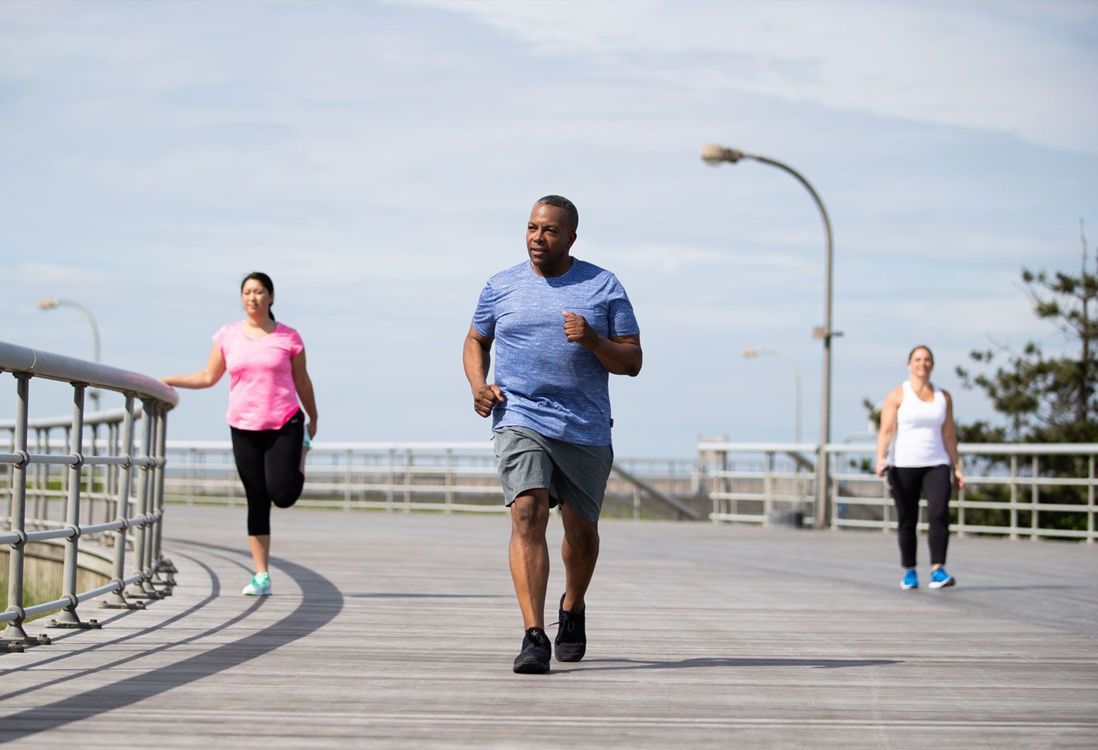 A middle aged man jogs on the beach boardwalk. There are two women out of focus behind him. One is walking and the other is stretching her leg. It's a bright, clear day.