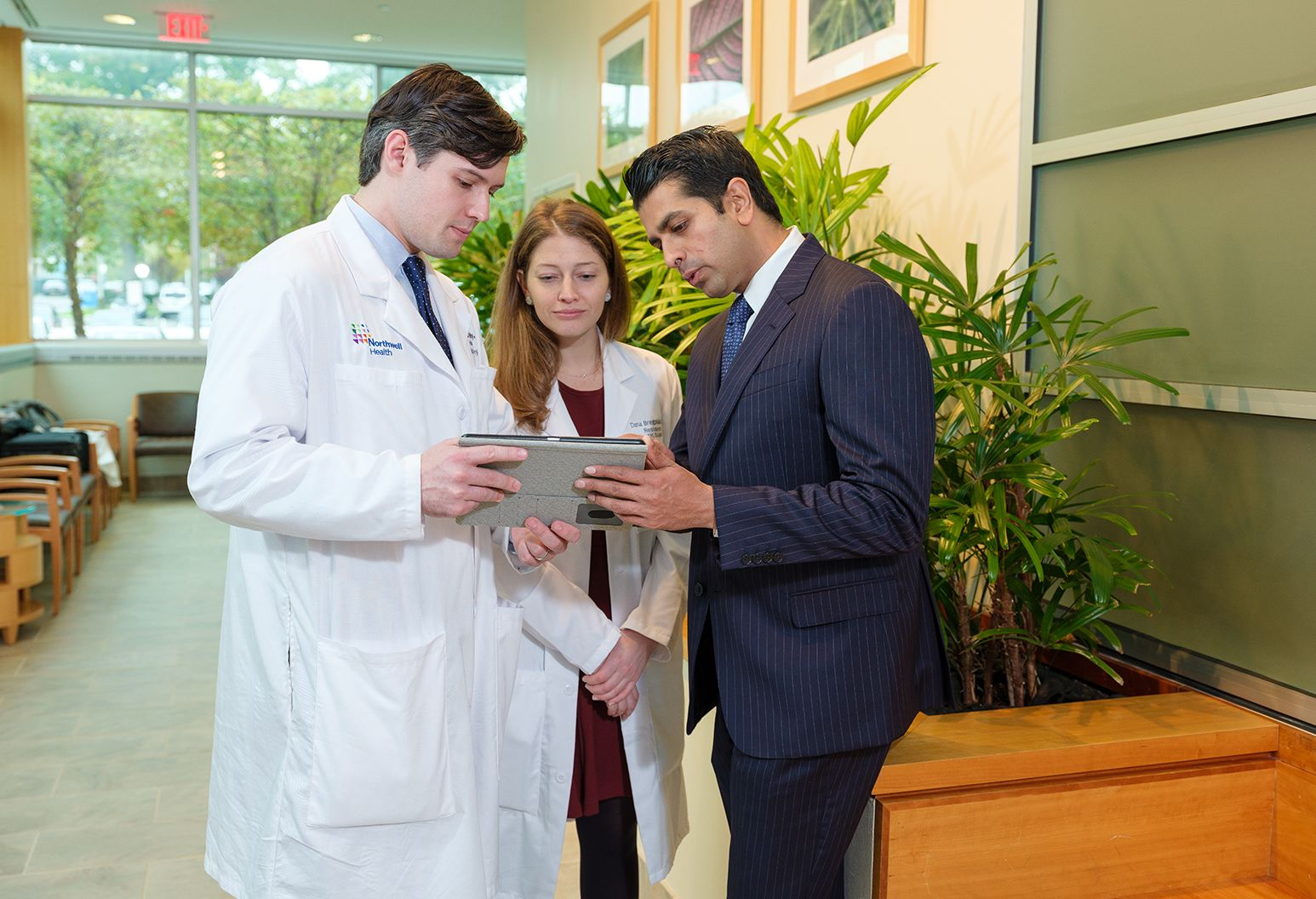 A male resident and female resident, both in white lab coats, review information on a tablet with a man in a navy business suit.
