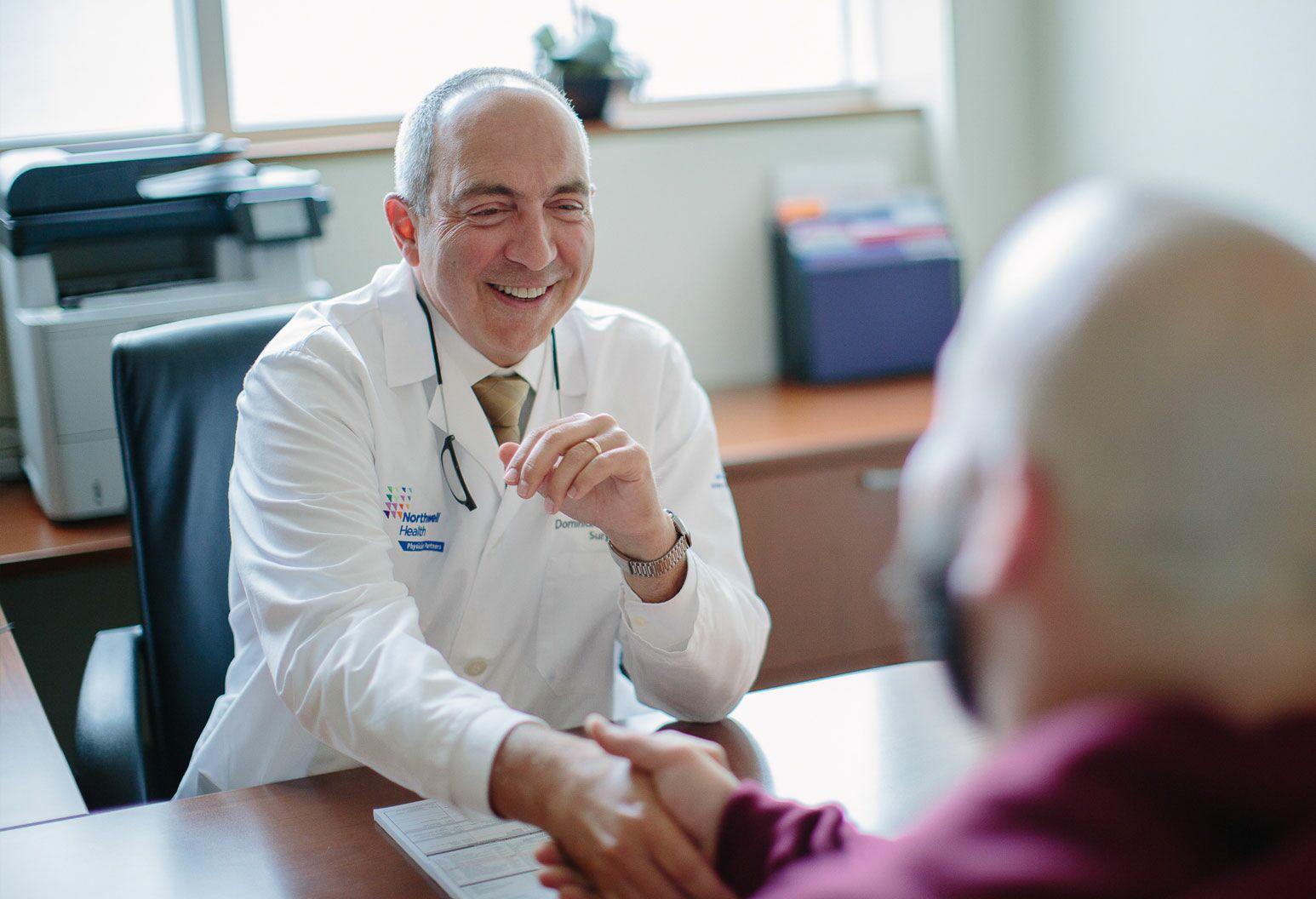 Doctor shaking patients hand across desk