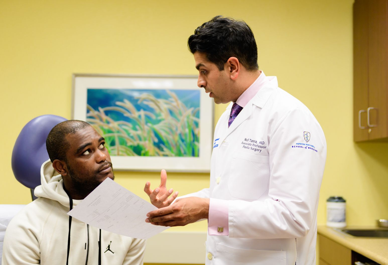 Man in white doctors coat holds a paper in his left hand as he explains something to an attentive dark-skinned male sitting in a purple chair.