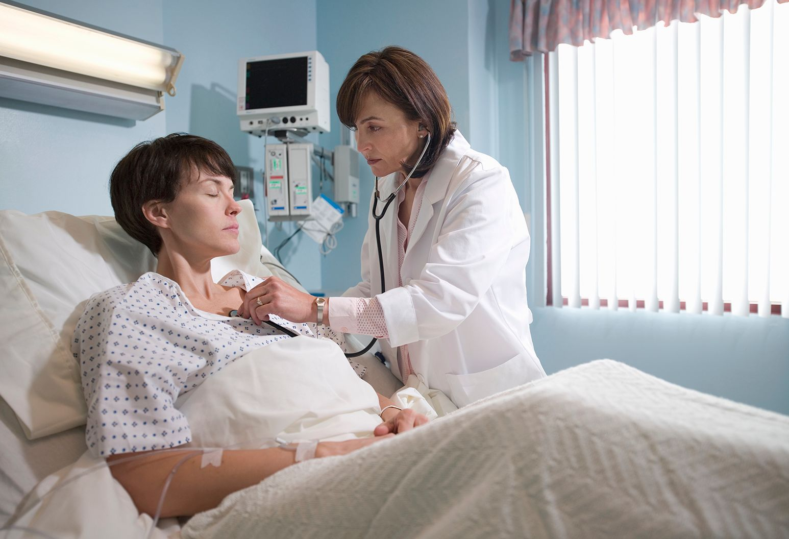 Female doctor examines female patient in hospital room
