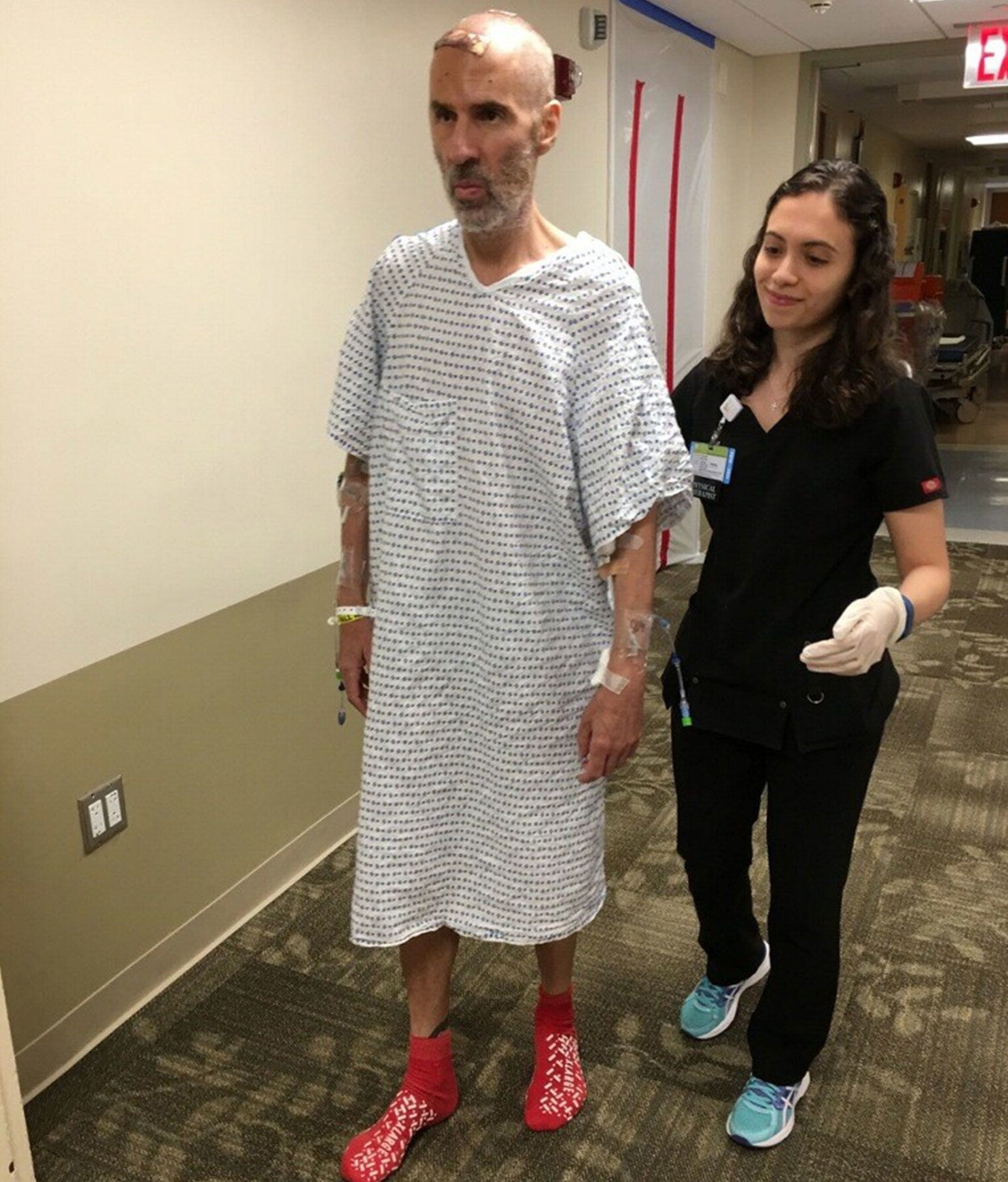 A man in a patient gown and red socks walks along a carpeted hallway. He has bandages on spots on the top of his bald head and along both his arms. A woman in a black nursing outfit walks along side him holding his back up with one arm.