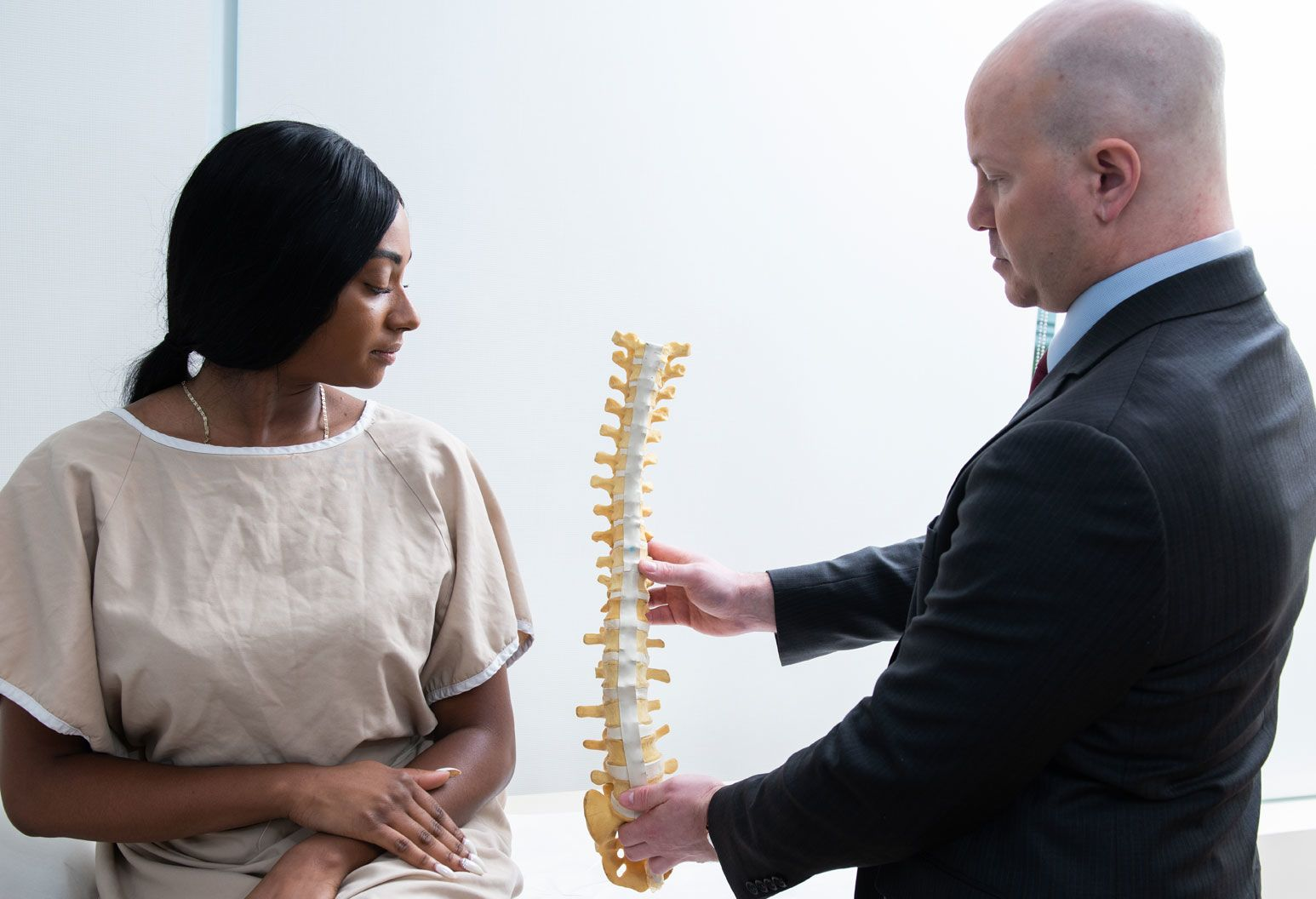 A doctor shows a model spine to a female patient wearing a patient gown.