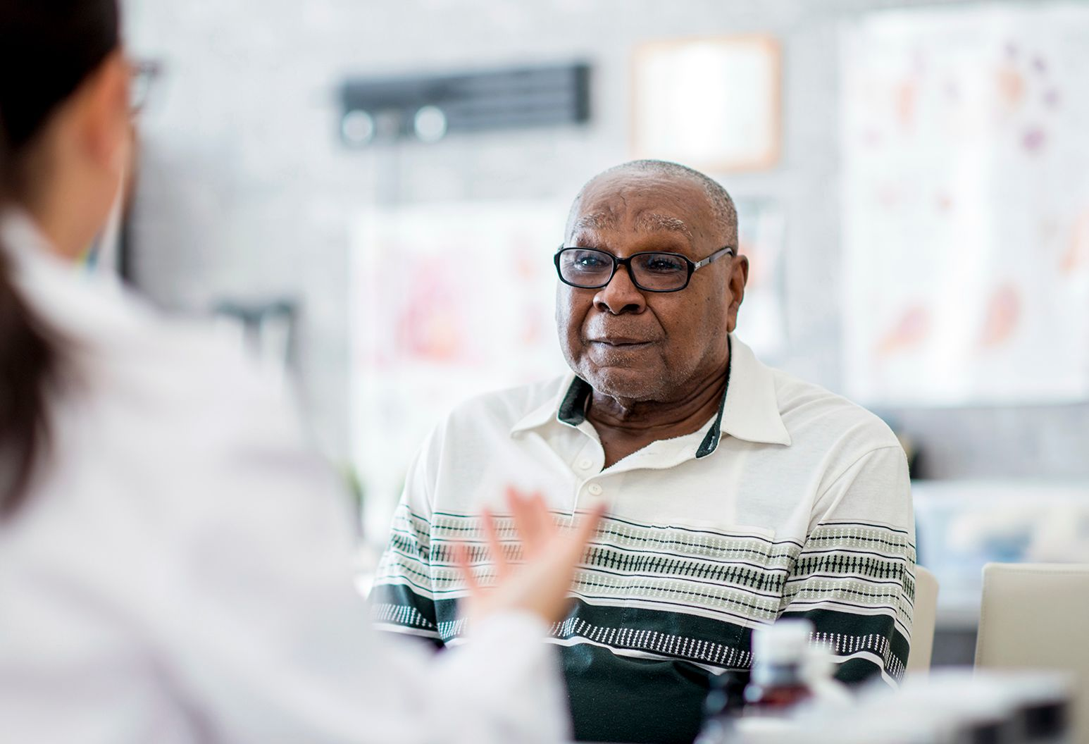 Elderly man with glasses listening carefully while a medical professional is explaining.