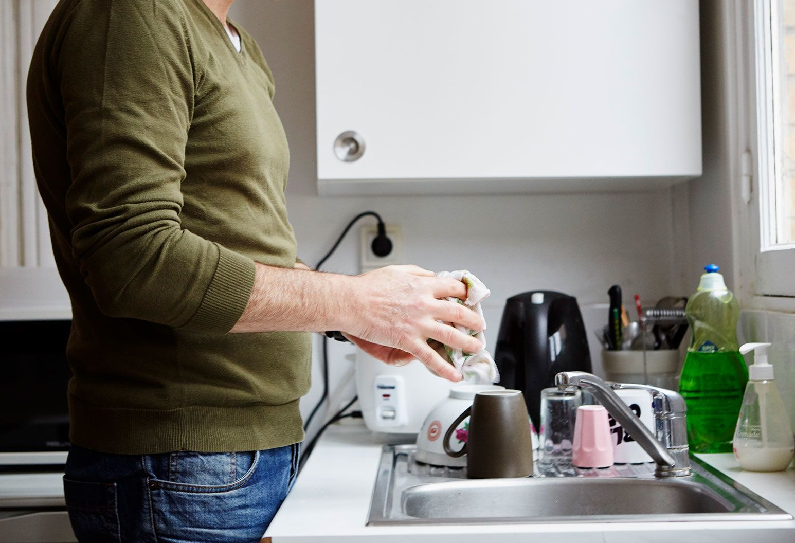 A man in a olive green sweater and blue jeans stands by the sink of a kitchen and cleans holds a wet rag over it.