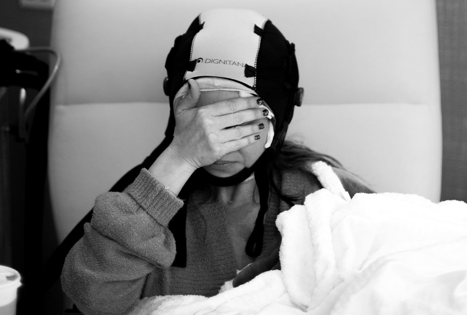 A woman sits in a padded chair covering her face with her hand. She also wears a cap over her head and appears to be in discomfort.