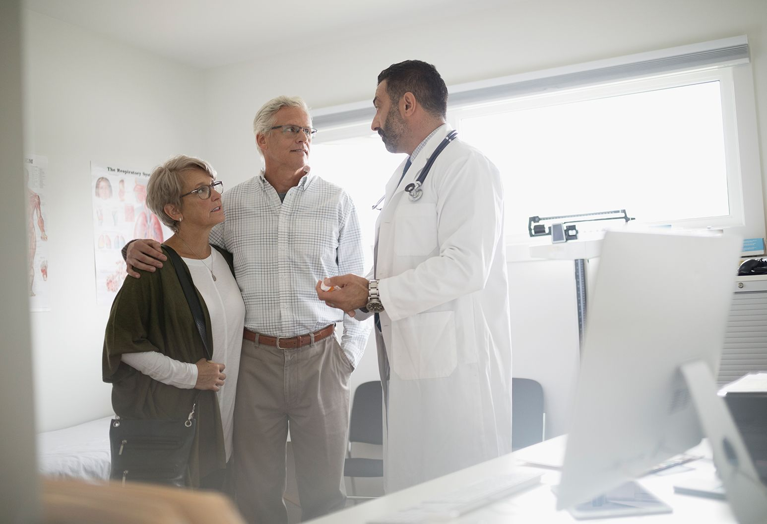 A doctor stands in his office consulting an elderly couple in glasses. The elderly man has his arm around an elderly woman as they hear the doctor discuss something with them.