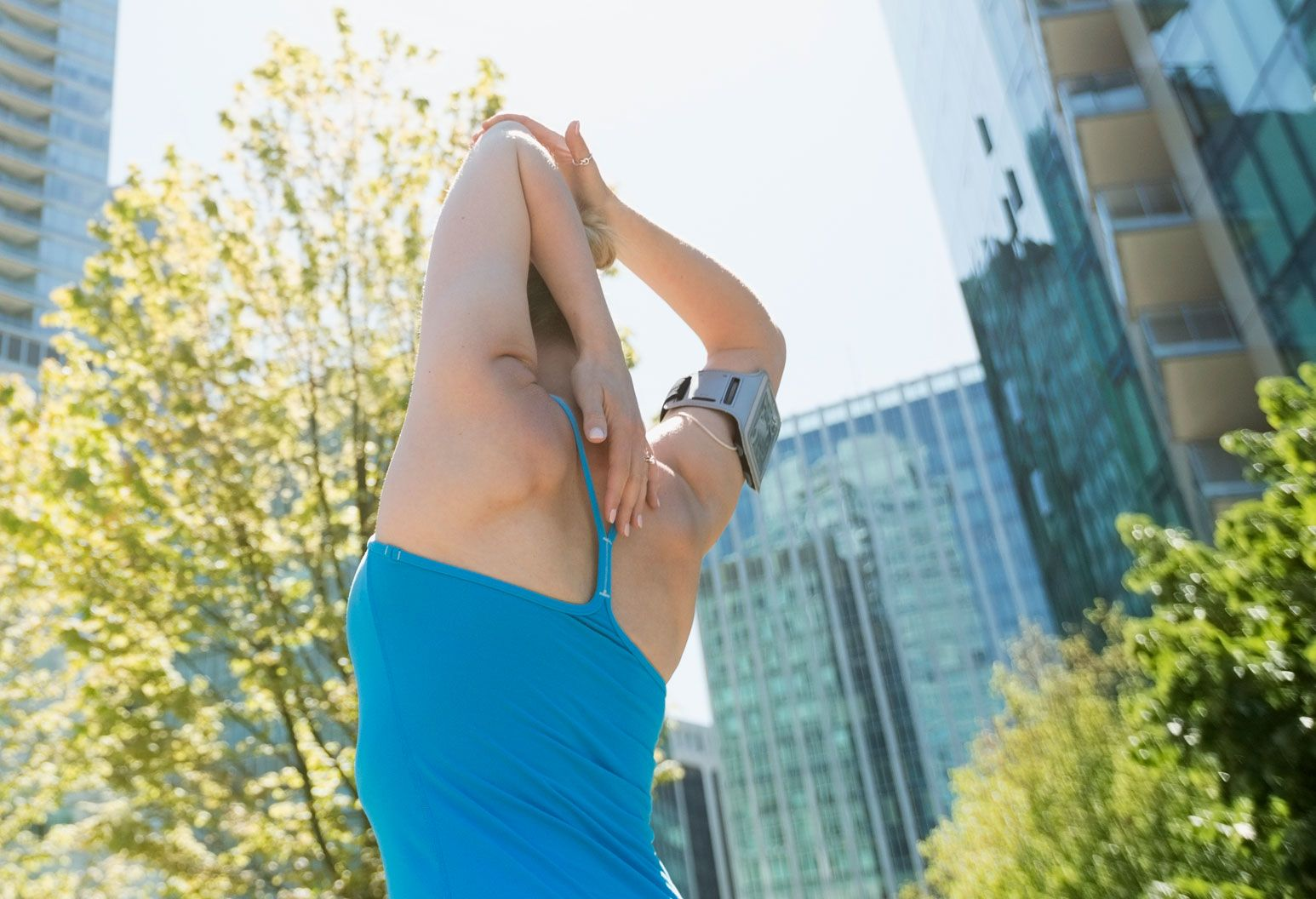 We see the back of a woman in a blue workout tank top, stretching her arm over her head. She is outside on a nice day.