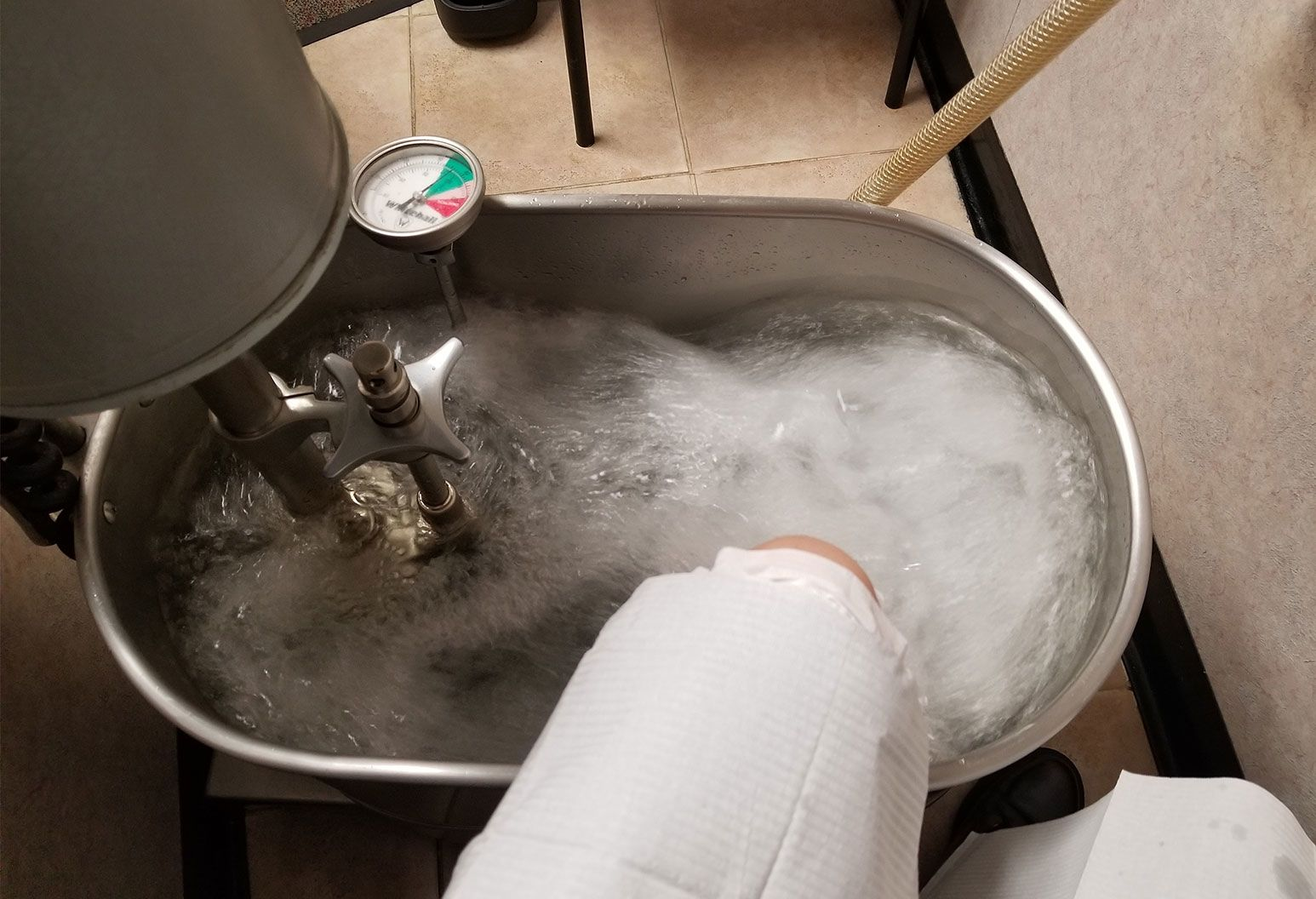 A foot is inside a silver tub filled with water. There are pipes and a gauge also in the tub causing as the water in the tub is bubbling up and whirlpooling around inside it.