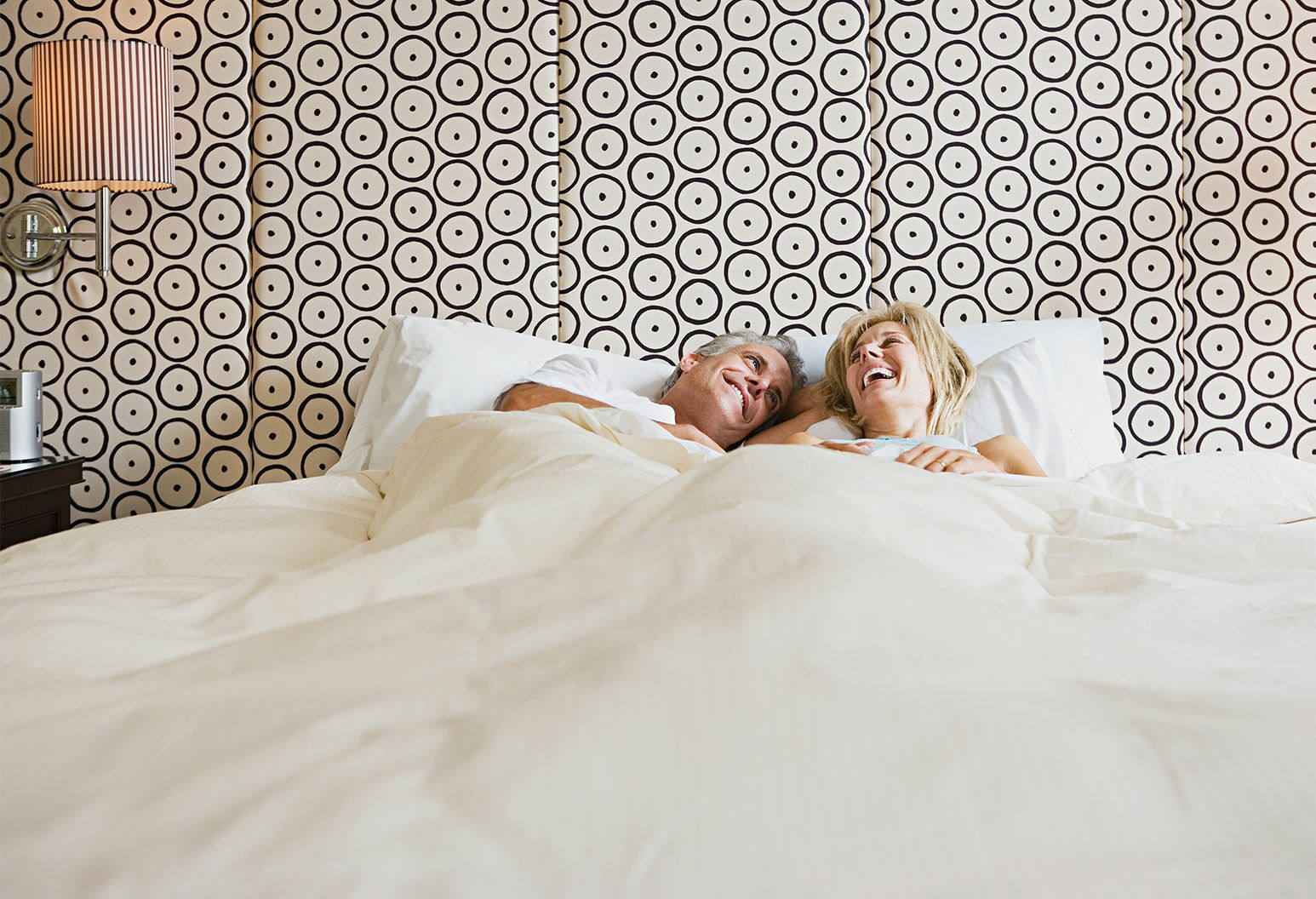 Mature couple in bed laughing under white sheeted covers against a circular patterned pleated wall.