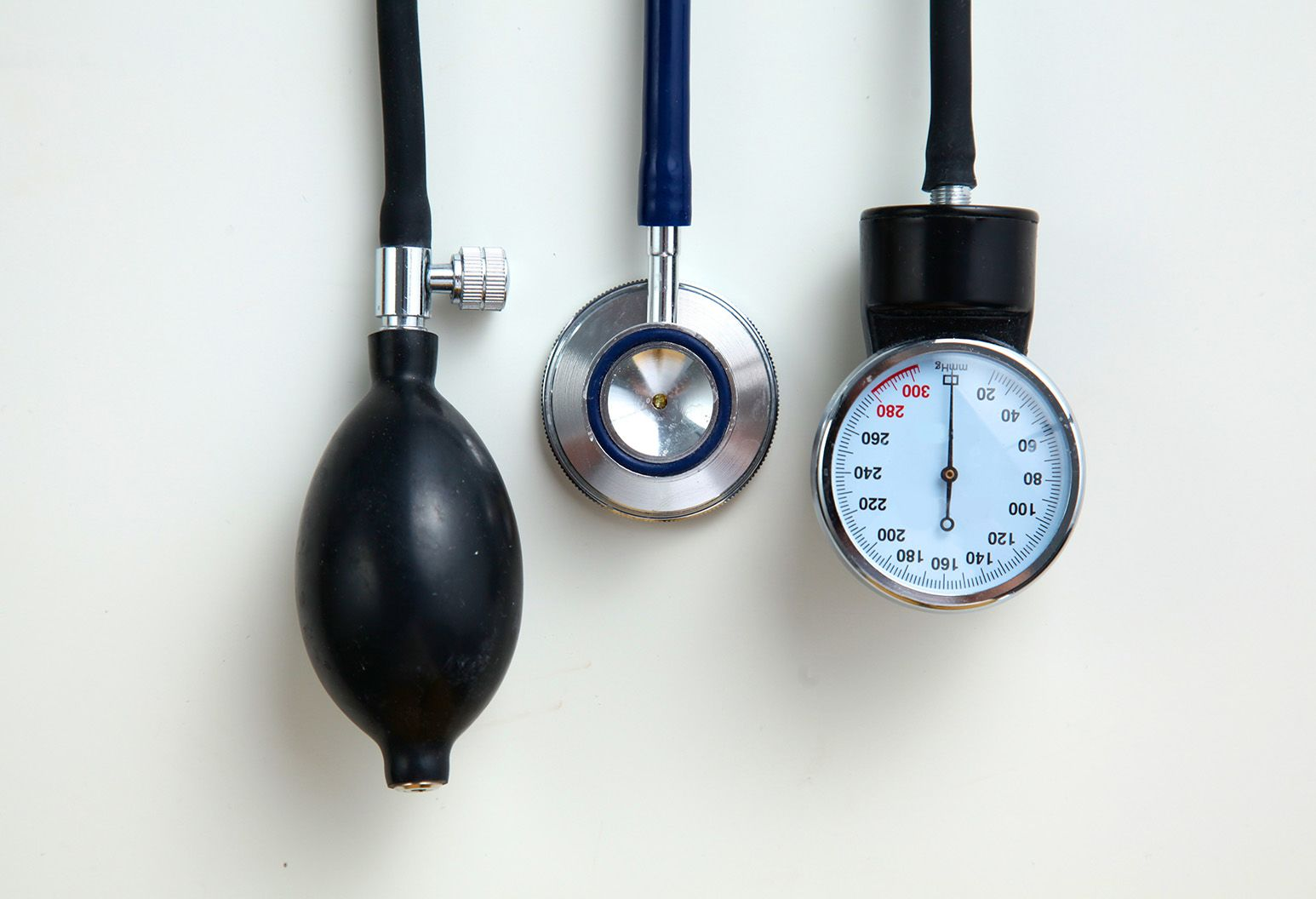 A blood pressure gauge and the end of a stethoscope hang on a wall.