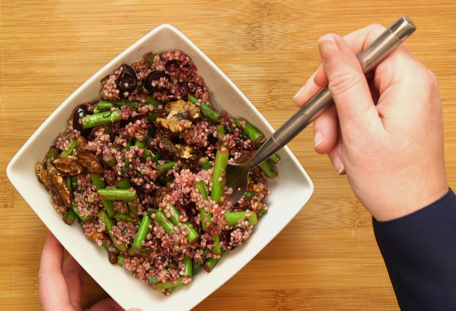 Quinoa salad with toasted walnuts and asparagus sits in a square white bowl on a wooden table. A hand holding a fork scoops some salad from the bowl.