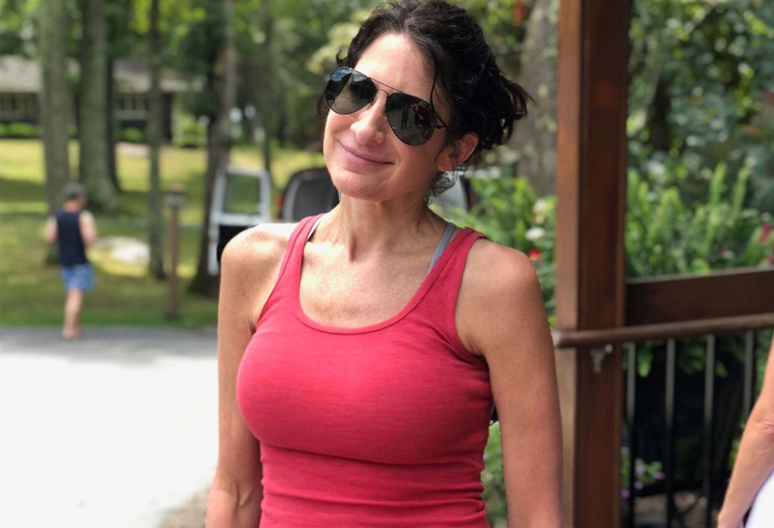 A woman stands outside smiling as she wears aviator sunglasses and a red tanktop.
