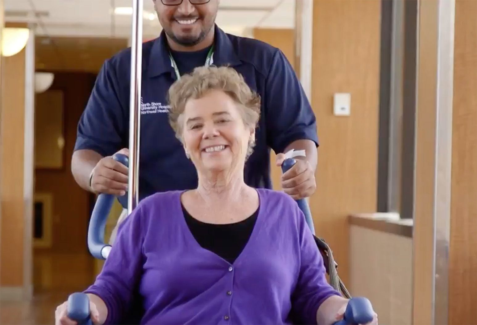 A smiling man in glasses and a navy polo shirt pushes a smiling elderly woman in a wheelchair.