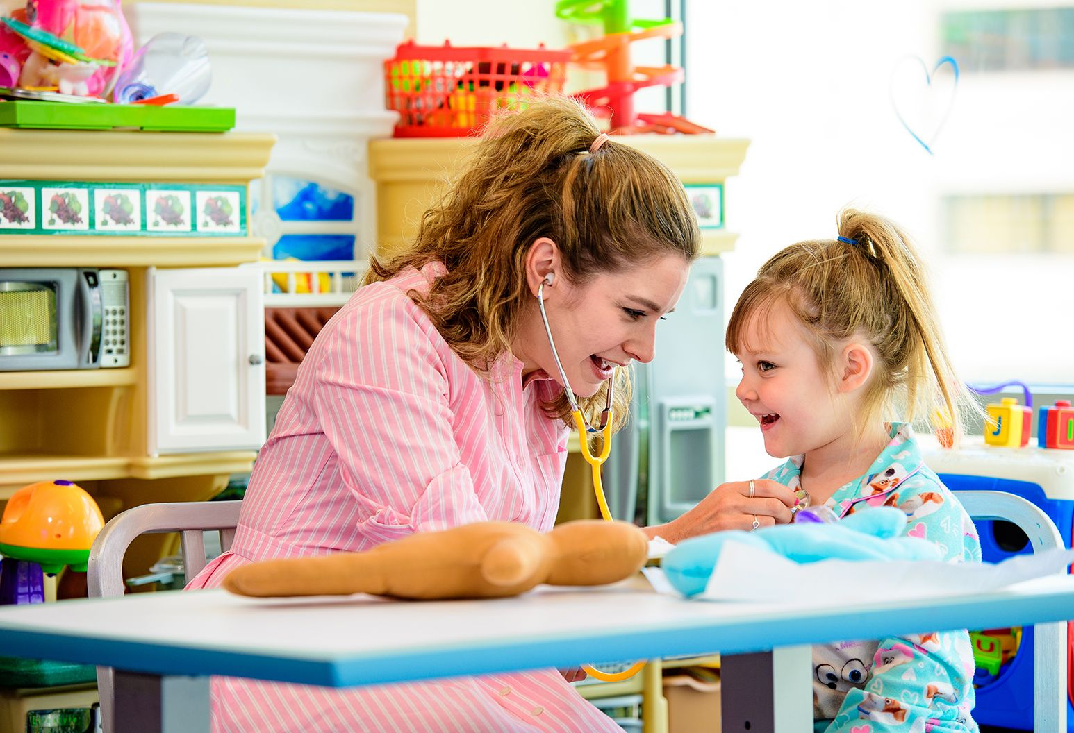A female child life worker in a pink and white striped shirt and a five-year-old female pediatric patient in blue patterned pajamas sit at a table in a colorful playroom at Cohen Children's Medical Center. They are both smiling as the woman listens to the girl's heartbeat with a yellow stethoscope. There is a medical doll on the table and toys in the background.