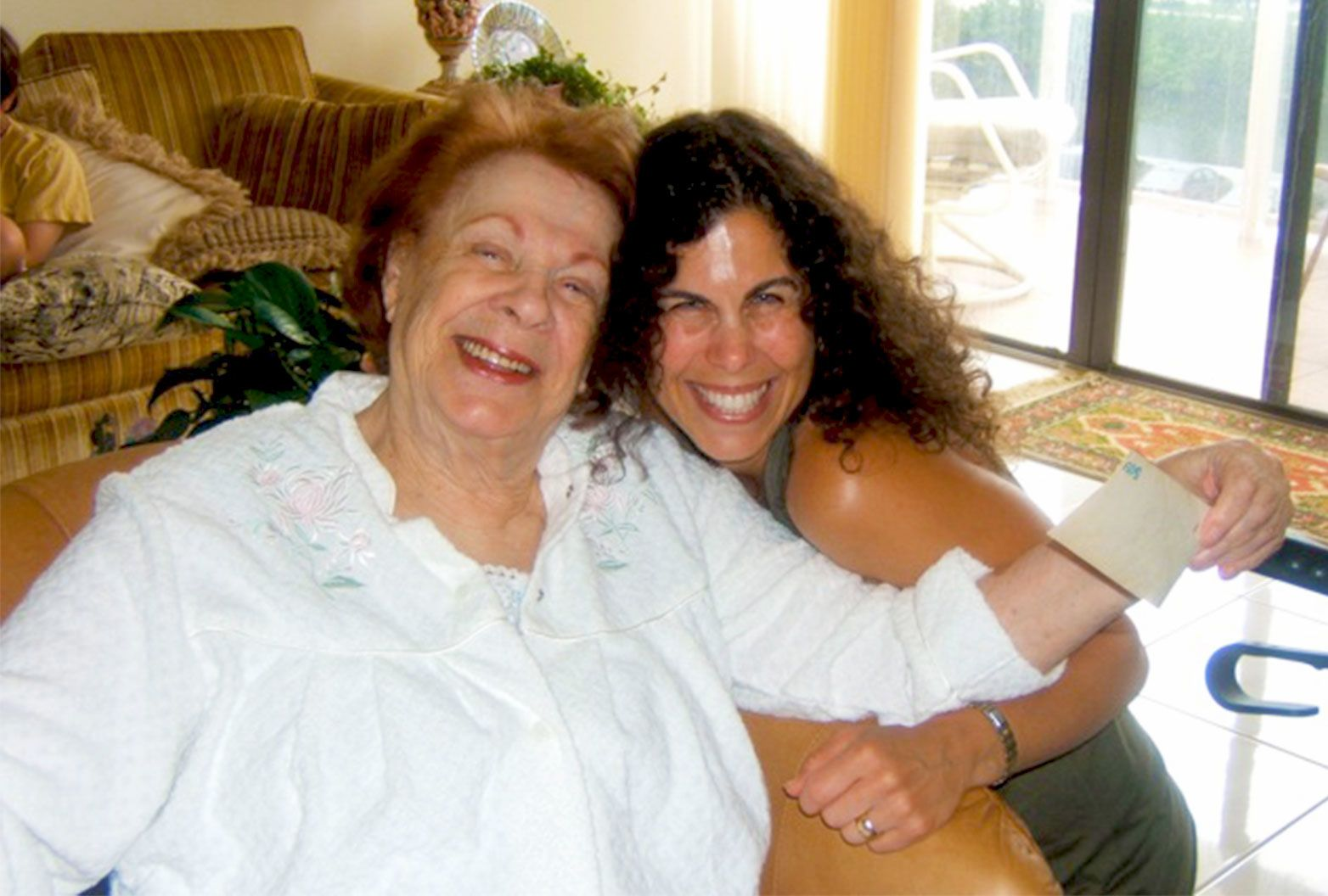 Woman with black hair poses for a photo beside an older woman with red hair and a white dress. They both have huge smiles.