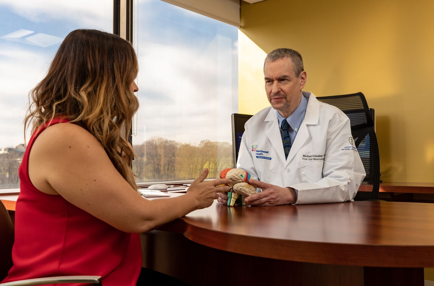 Michael Schulder, MD, sits with a female patient