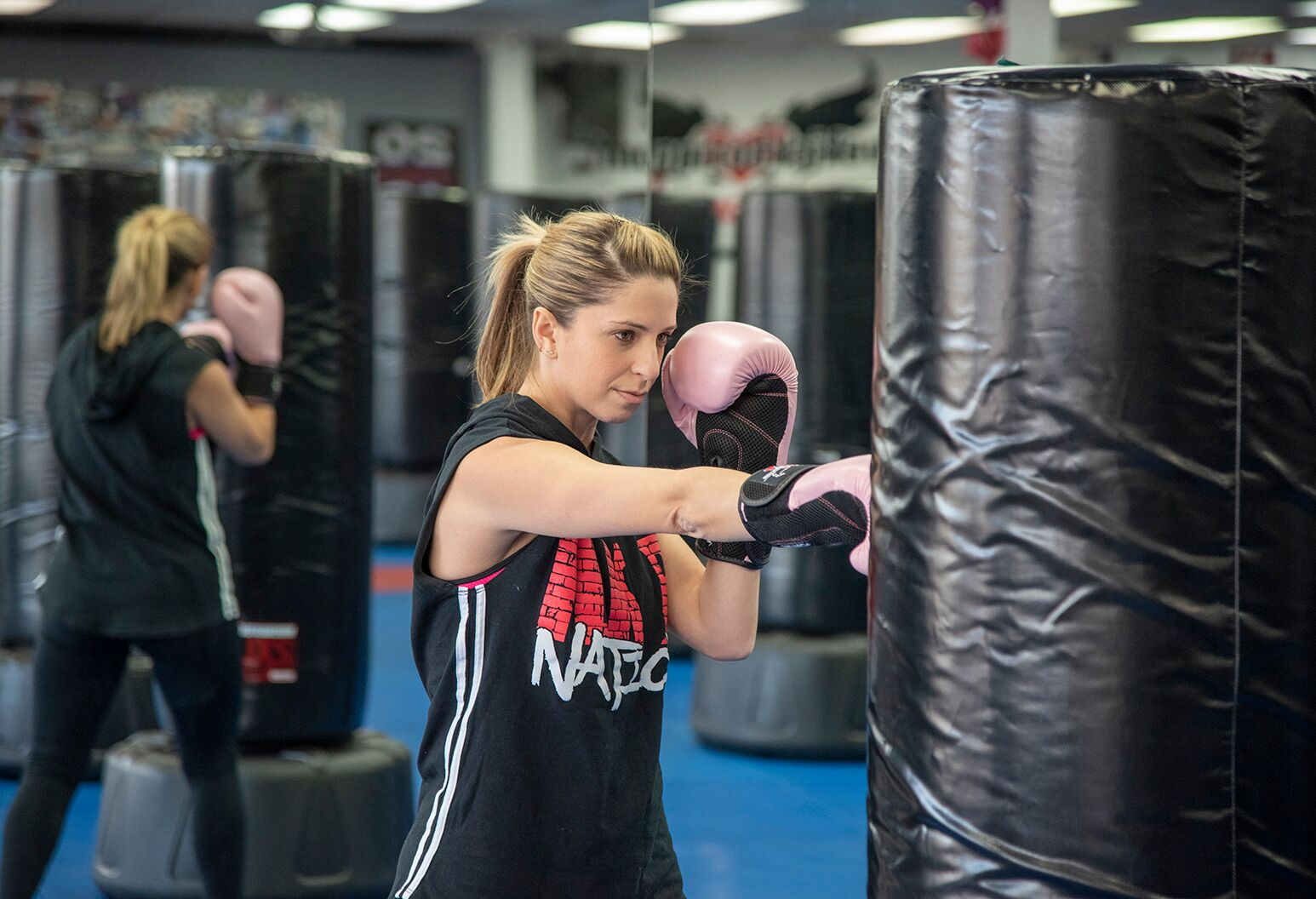 Woman in her 30s punches heavy bag in a gym.