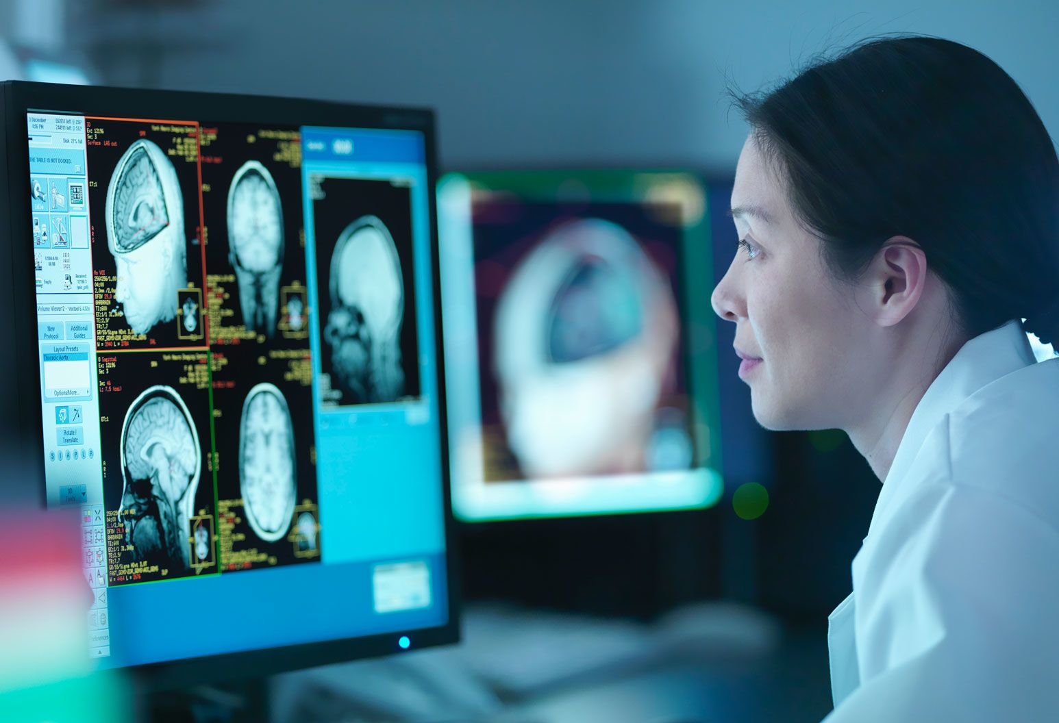 Female physician looking head scans on monitor