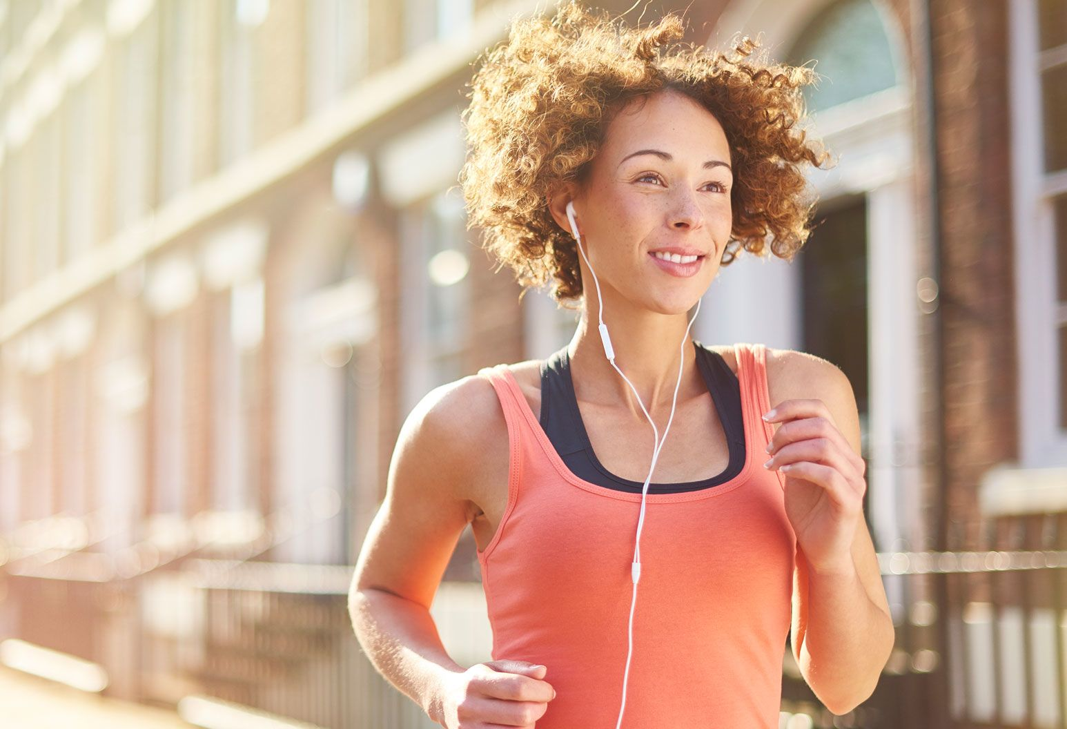 A woman jogs outside on a nice day. She wears a bright tank top and headphones.