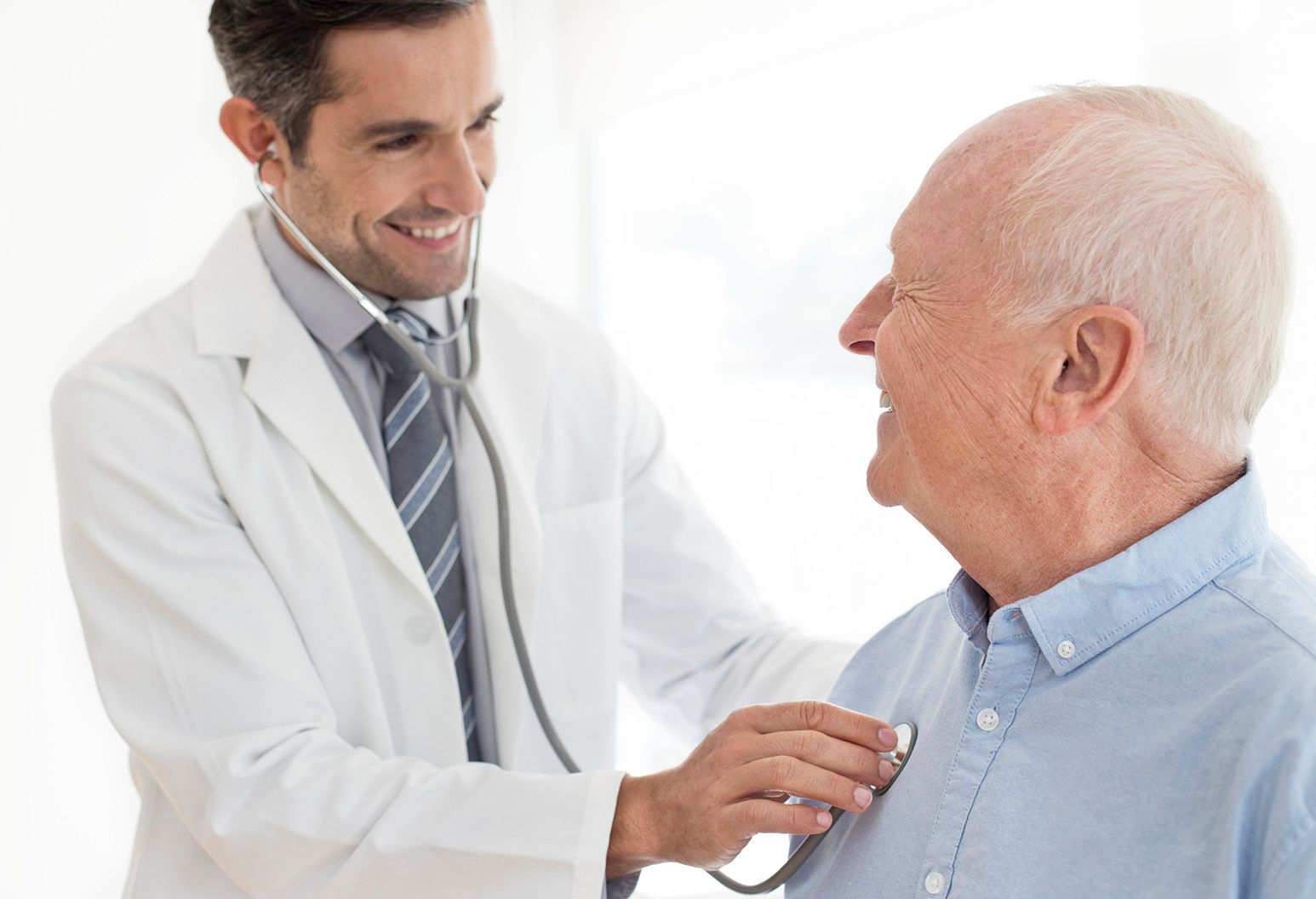 Older man with gray hair and blue shirt smiles as male doctor with brown hair listens to his heart with stethoscope.