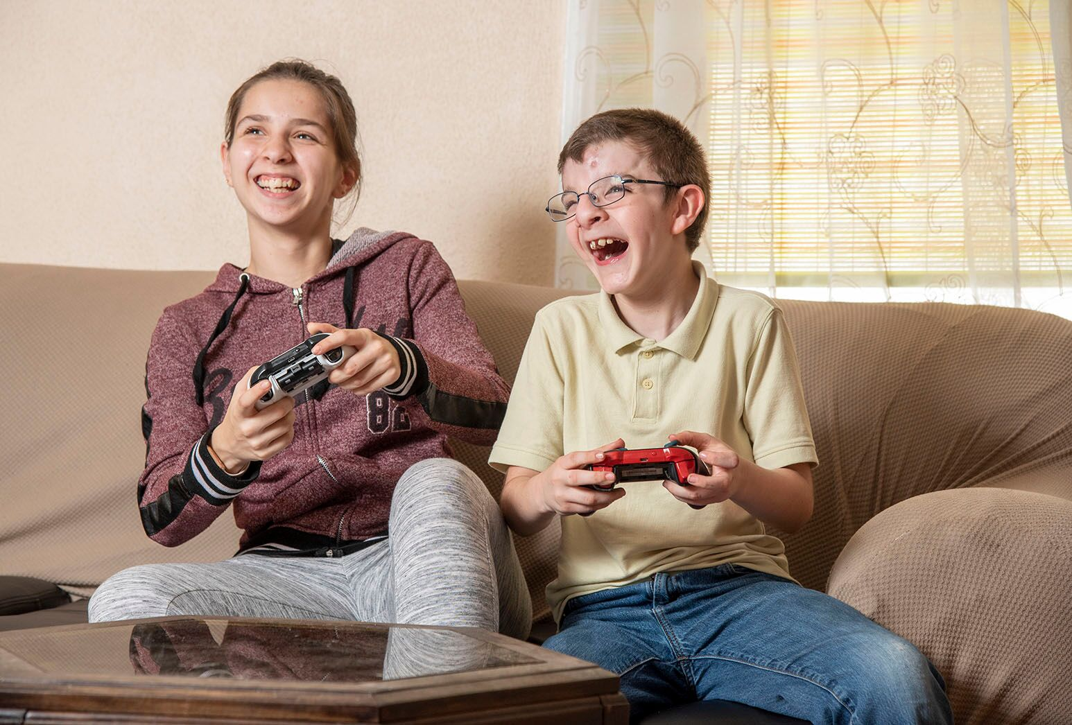 Girl with brown hair and burgundy sweatshirt and boy in yellow shirt play video games on brown couch
