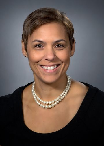 Zenobia Brown, MD, wearing a black shirt and pearl necklace
