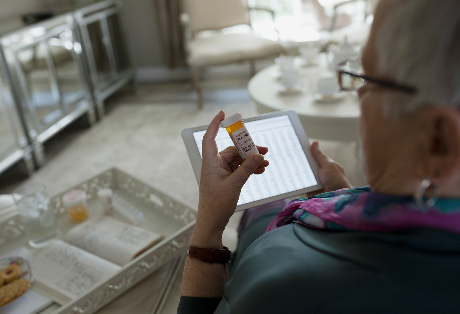 Senior woman with digital tablet checking prescription label.