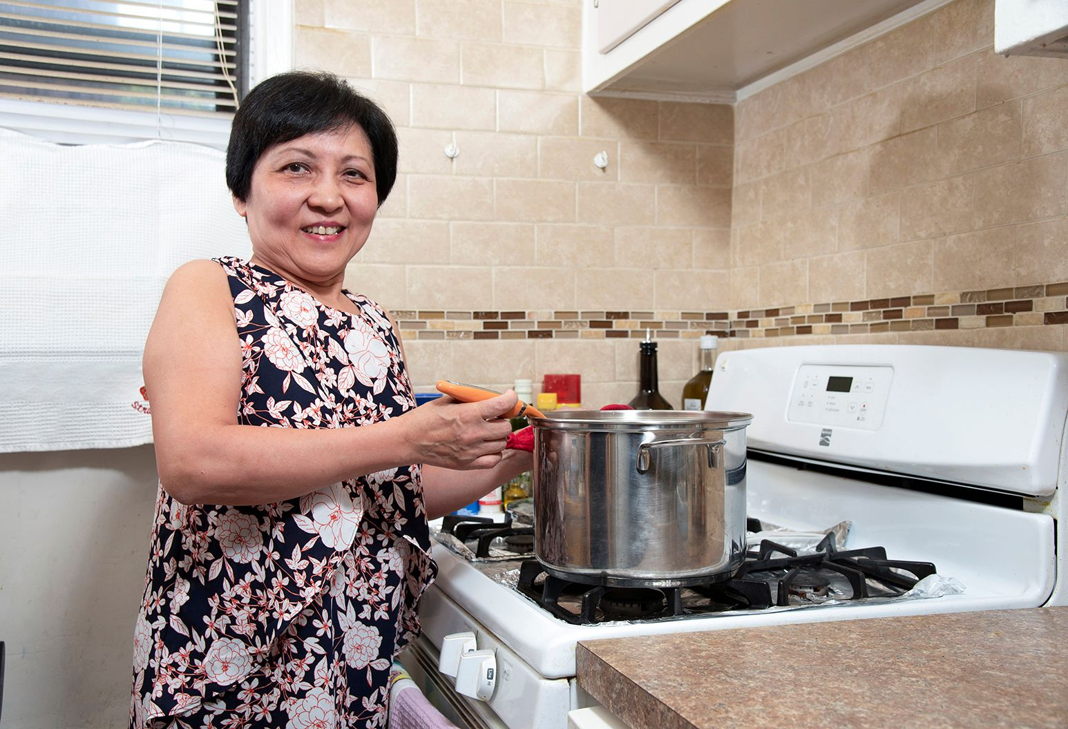 Chen Lie, a patient participating in a robotic stroke rehab clinical trial at the Feinstein Institute, cooking in her kitchen.