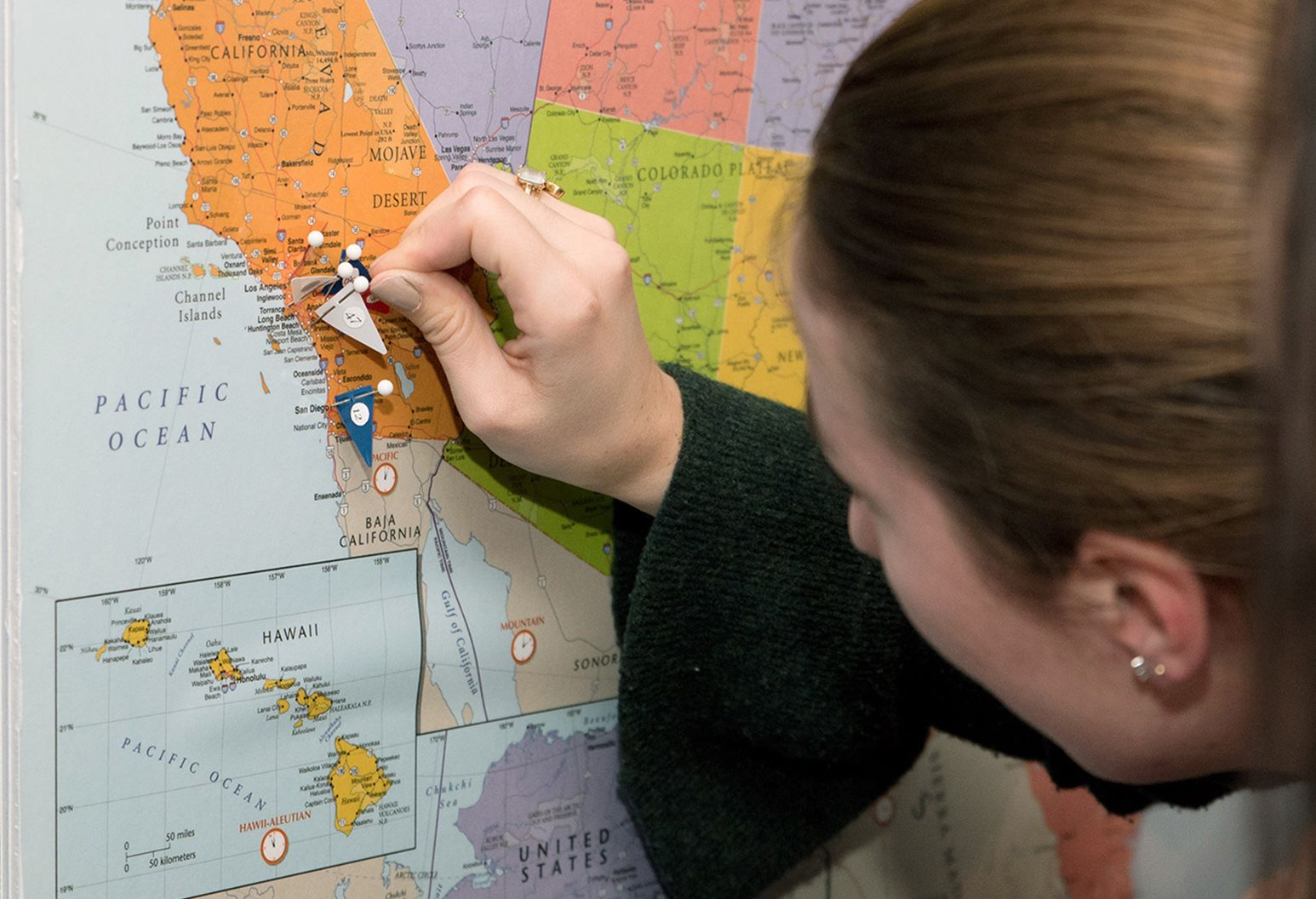 Women placing pins on a map of the United States.