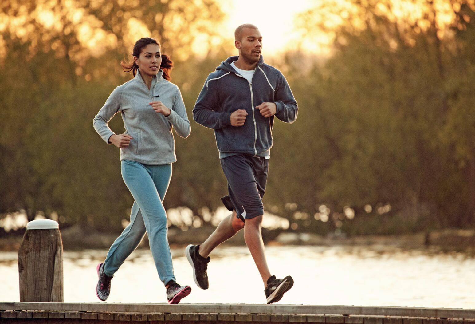 A black man and woman run on the dock of a lake. Robert Trasolini, MD, explains why hip arthroscopy has become an option for everyday athletes.