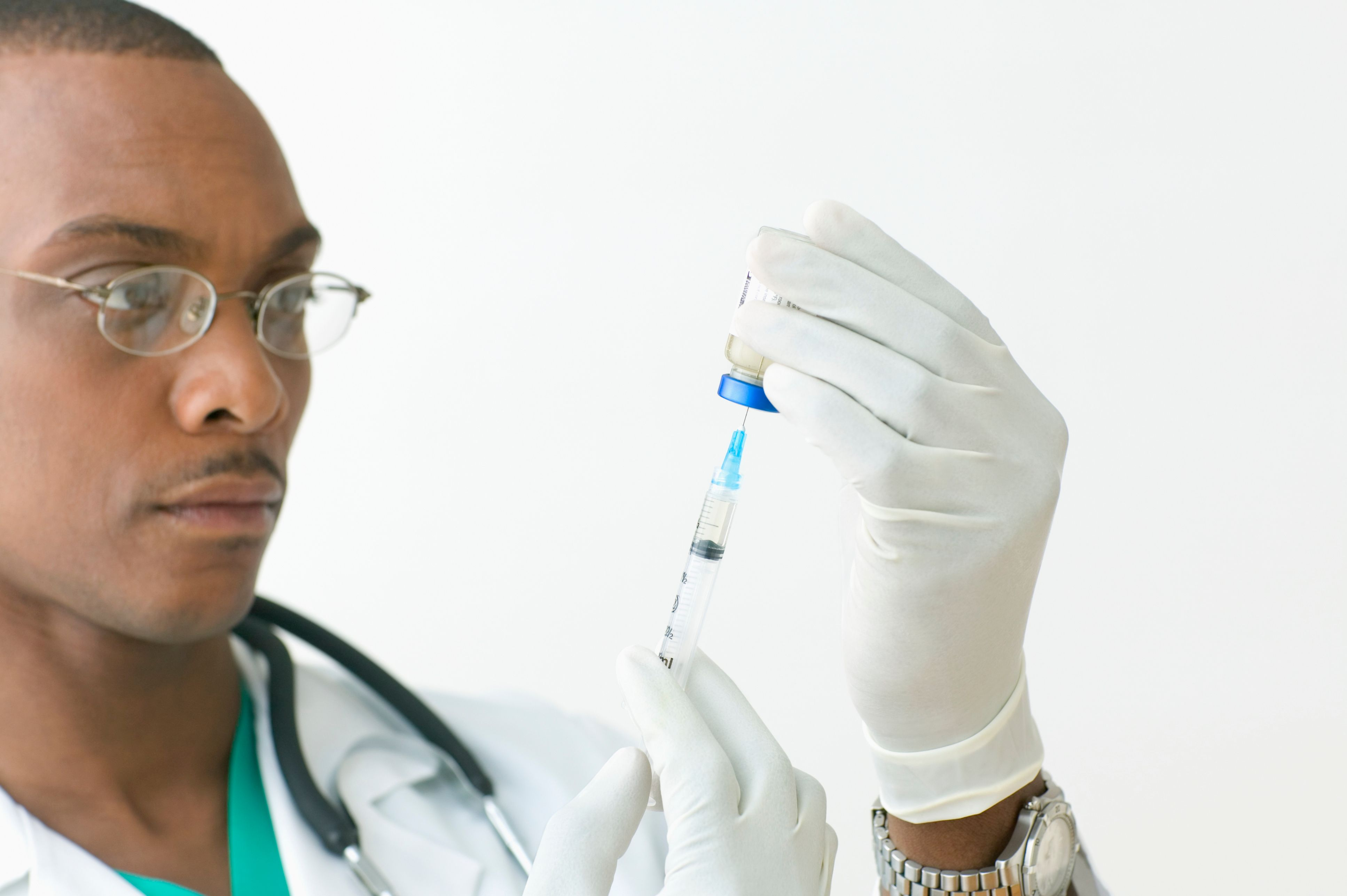 A doctor loads a vaccine