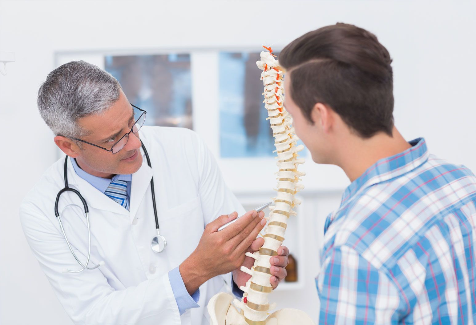 A doctor wearing glasses and a white lab coat holds a model of the spine and points to it, explaining something to a patient. The male patient listens and smiles. He is wearing a blue flannel shirt. There are x-rays blurred in the background.