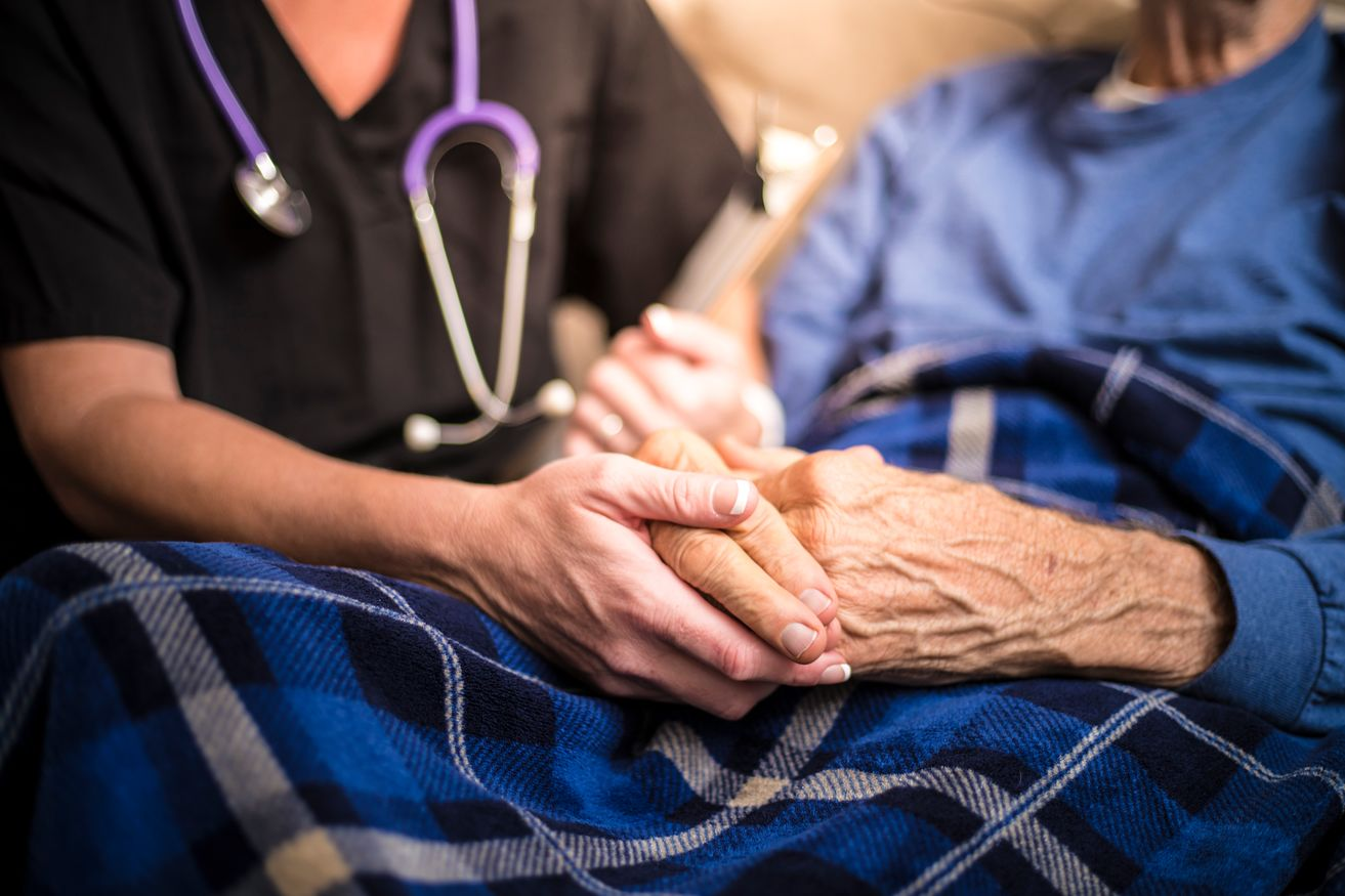 A nurse holds an elderly person's hand