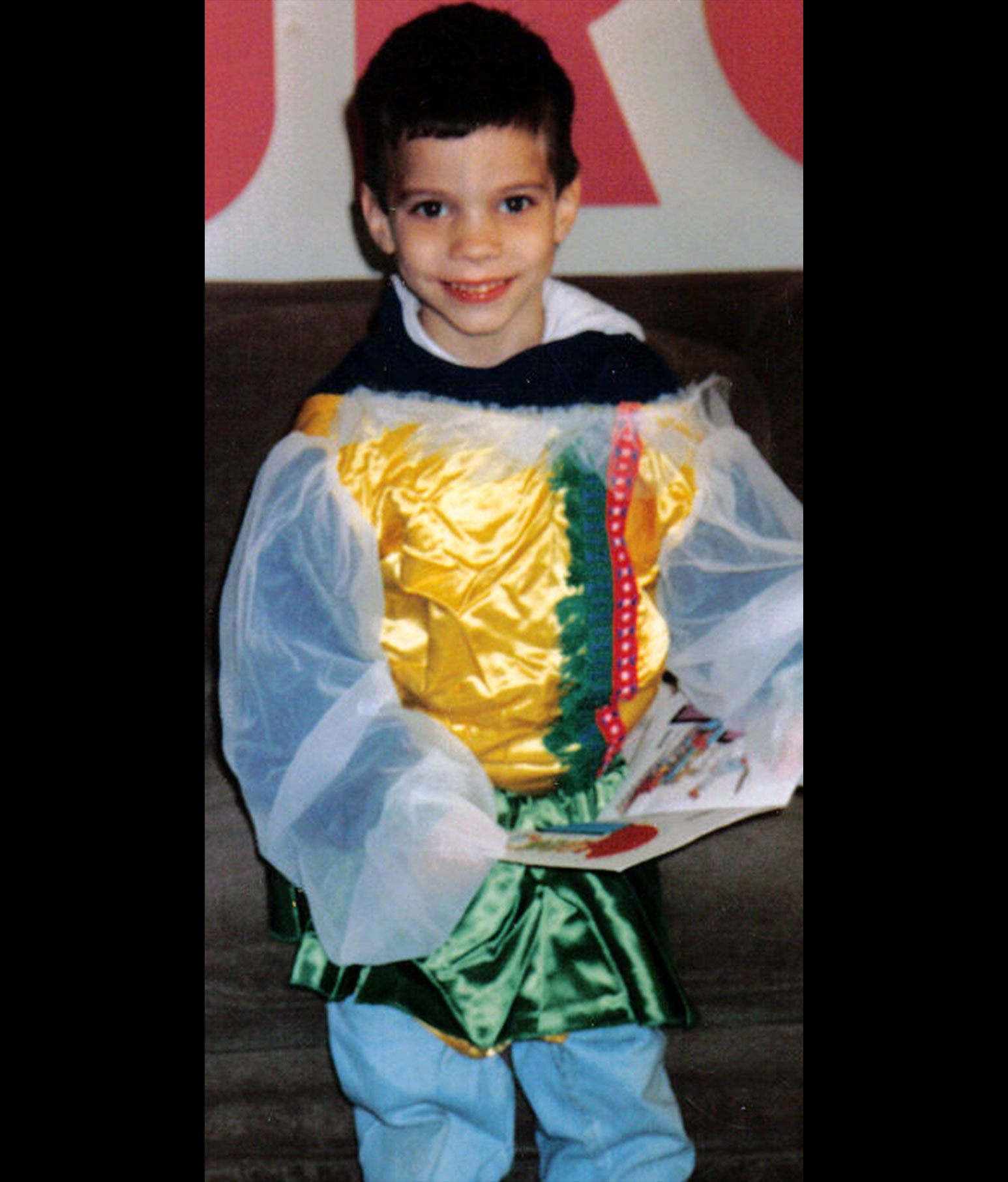 An old photo of a young boy smiling at the camera as he wears a jester outfit.