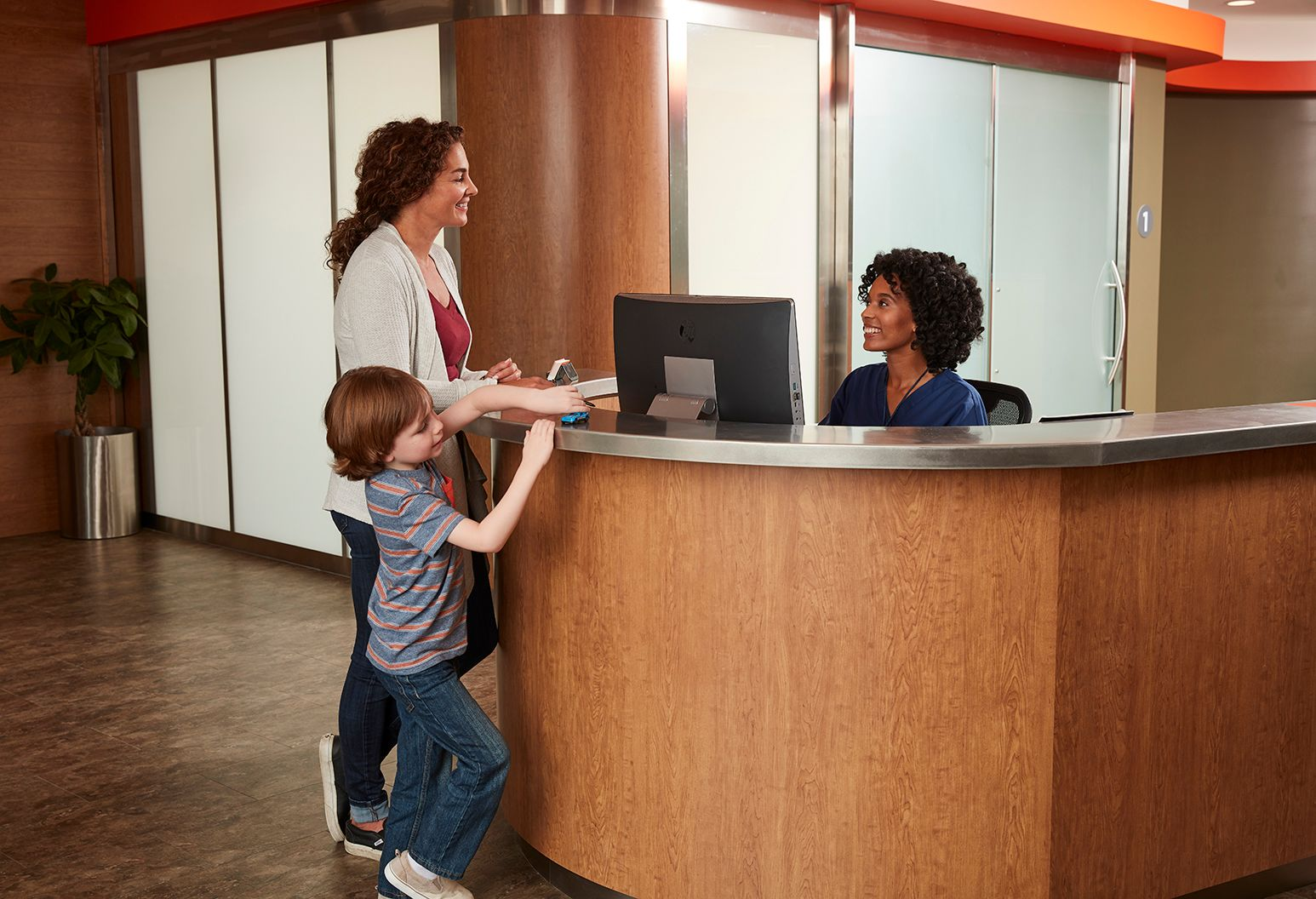 Woman and child at reception desk, talking to receptionist