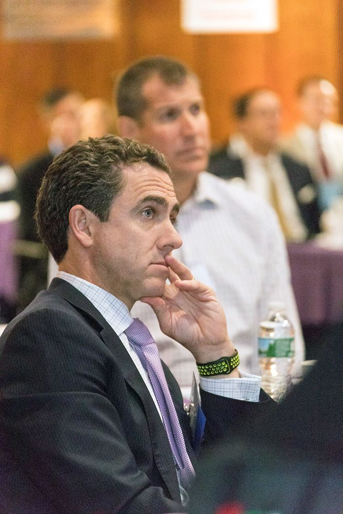 Middle aged man wearing a suit is watching a presentation at a conference