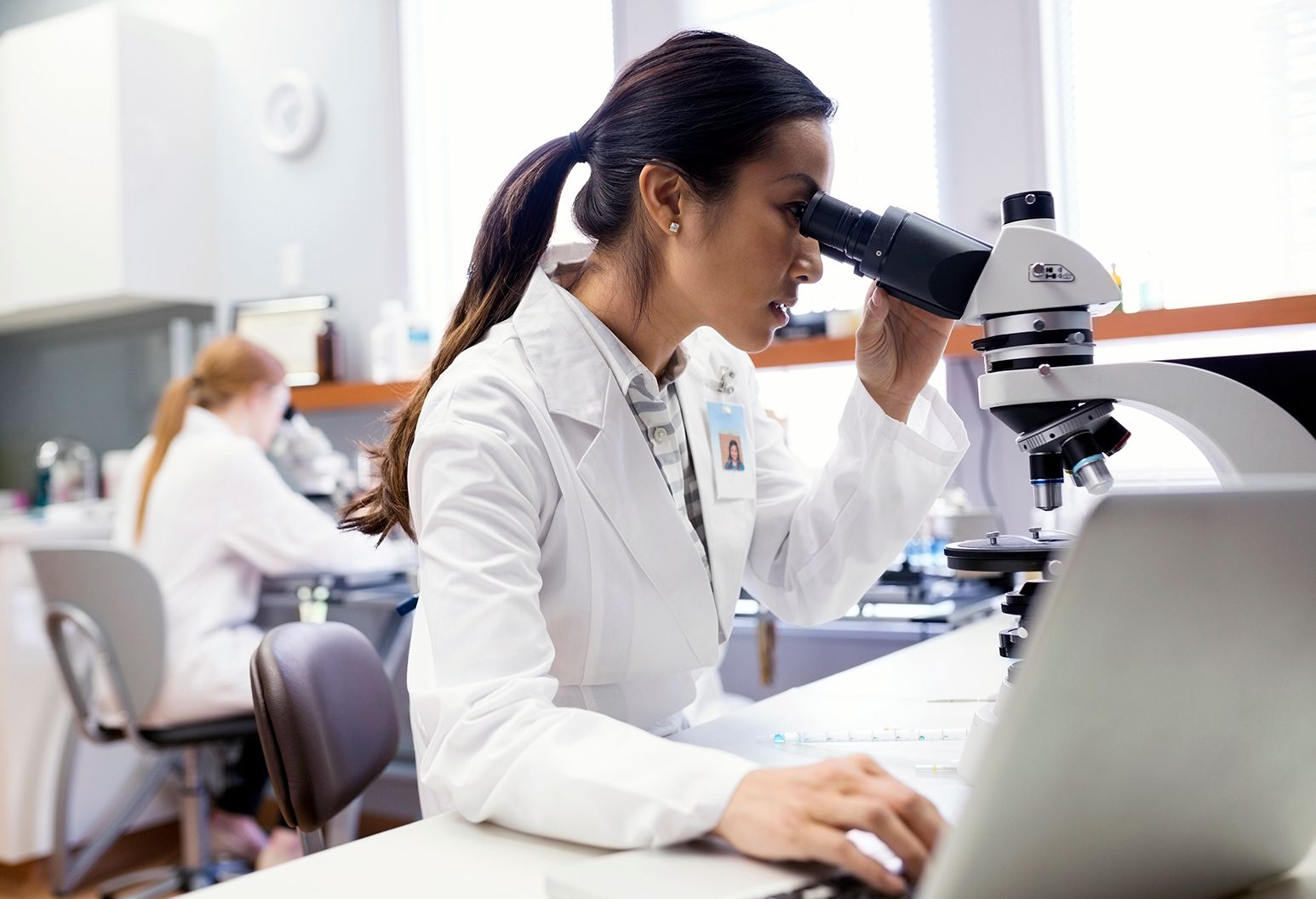 Medical scientist using microscope near laptop in laboratory