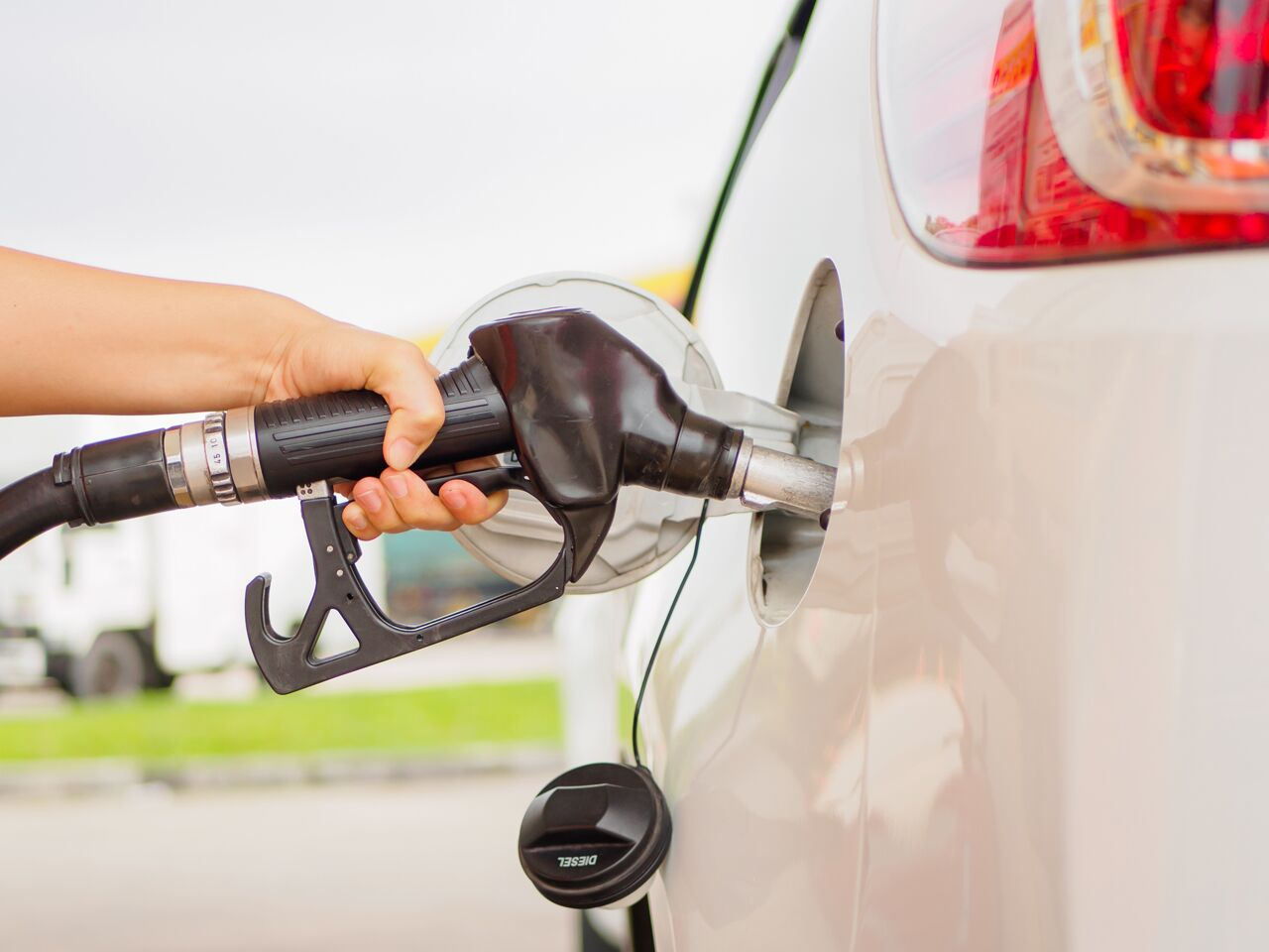 Hand holding black gas pump while pumping fuel into white vehicle.