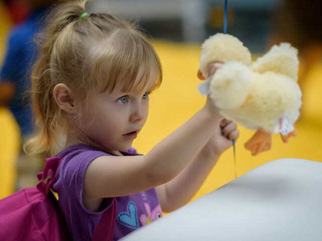 "alt=""young girl mesmerized by stuffed toy duck"""