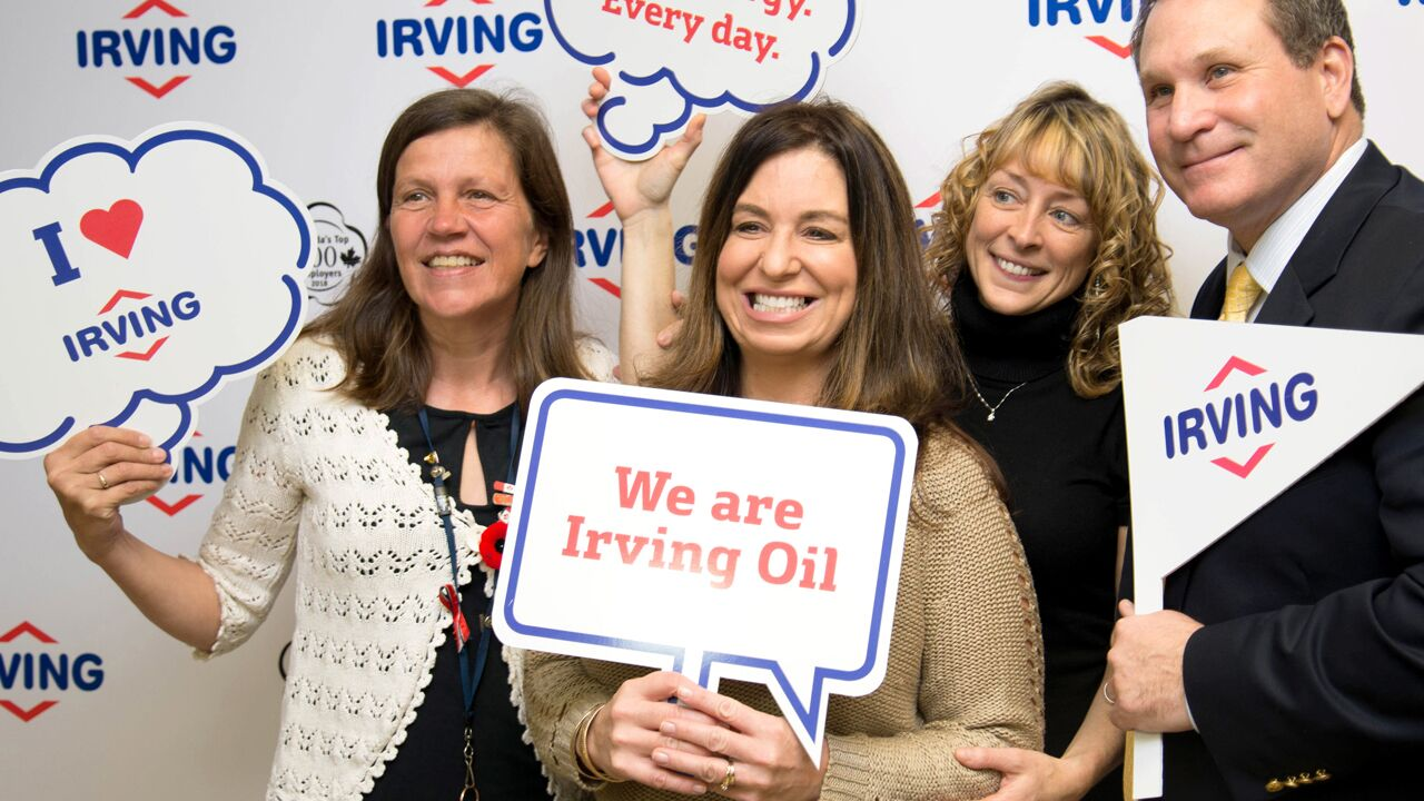 "alt=""smiling employees posing with Irving branded signs"""