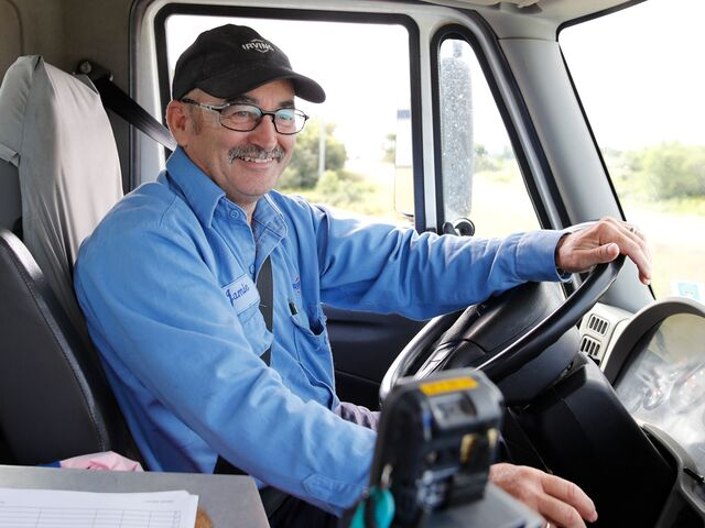 "alt=""smiling truck driver in drivers seat"""