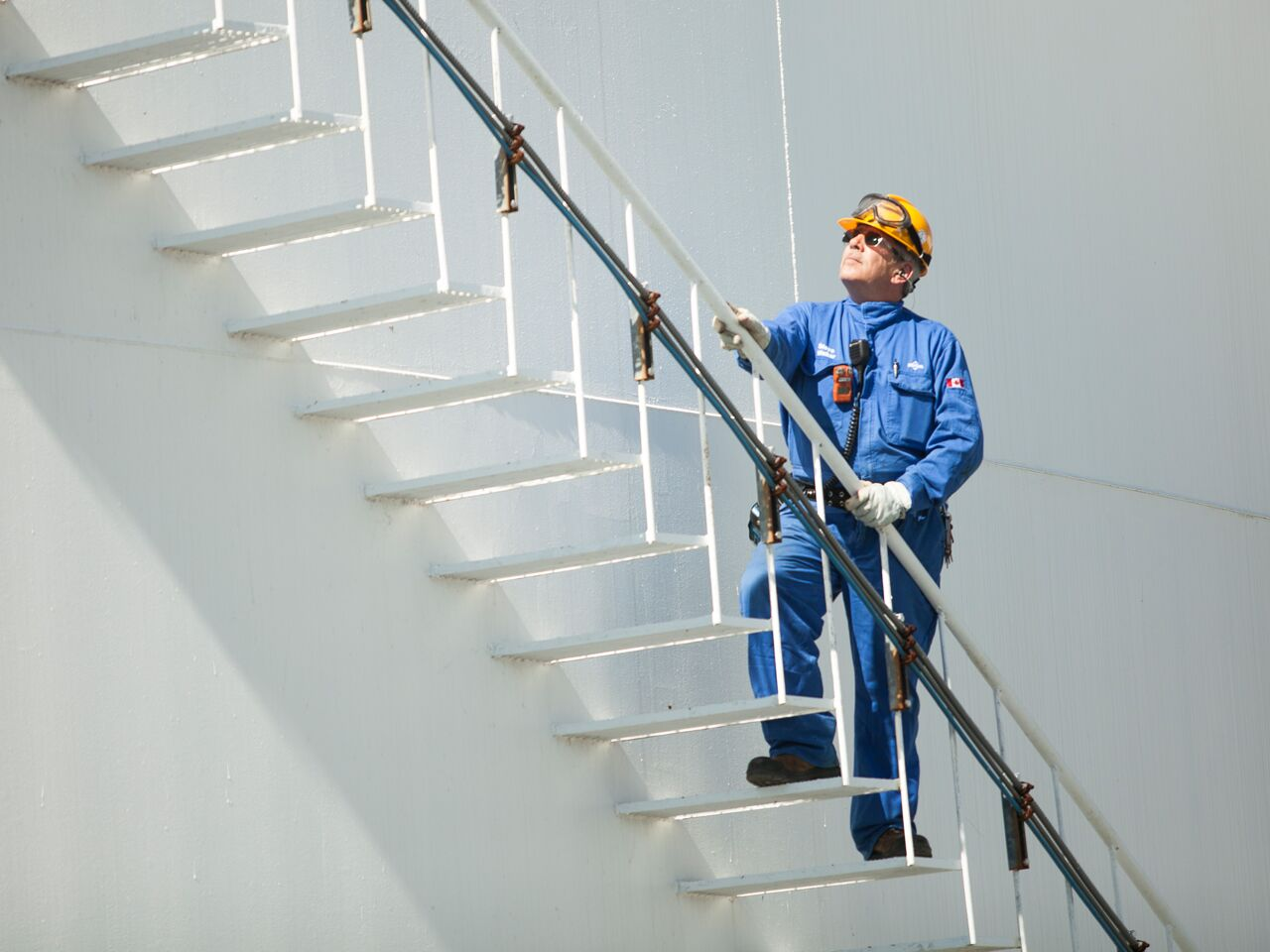 "alt=""refinery worker climbing staircase outside"""