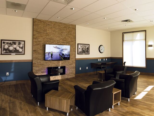"""alt=""""black leather couches facing television in lounge"""""""