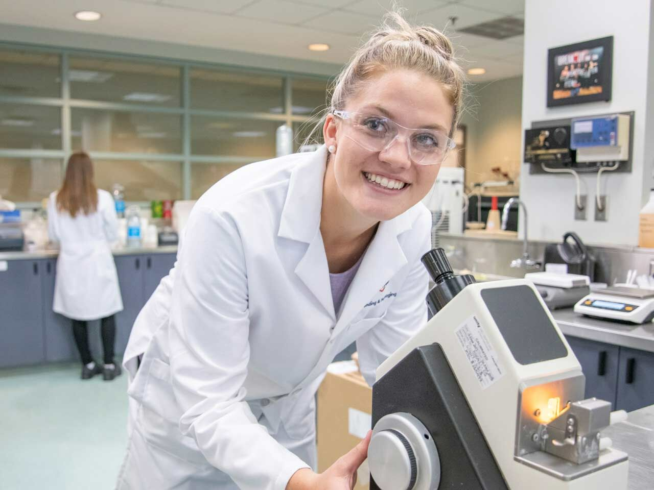 "alt=""female lab technician smiling over microscope"""