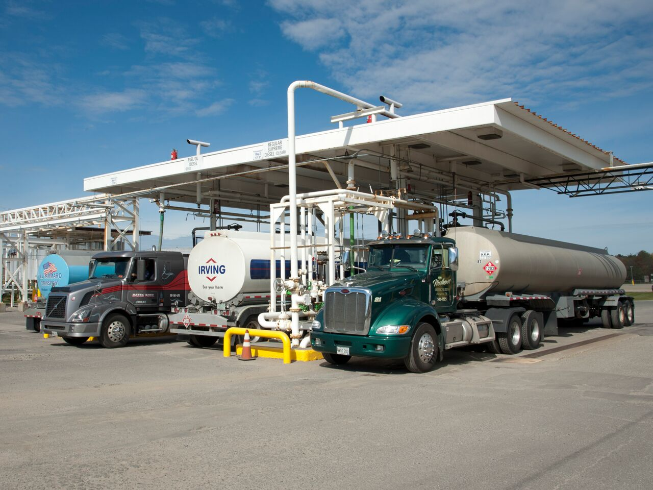 """alt=""""transport trucks being filled with oil products"""""""