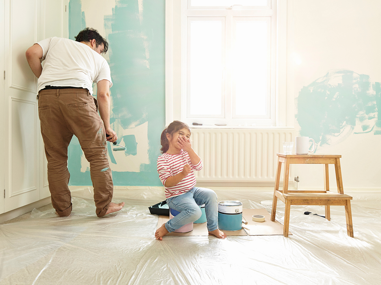 Daughter laughing while dad decorates wall in domestic home