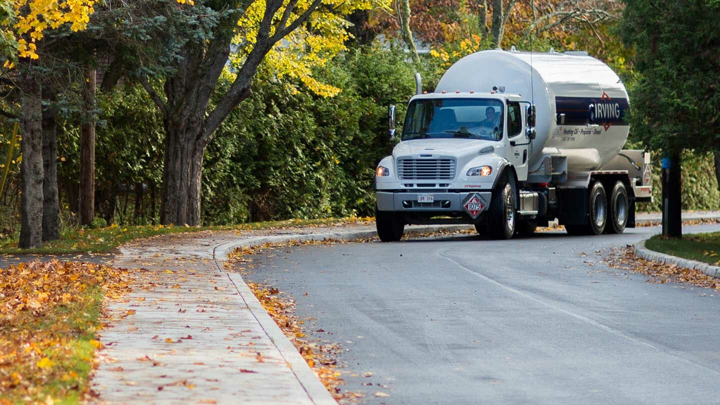 Irving Energy fuel truck parked on the road surrounded by leafy trees and multicolored leaves on the ground.