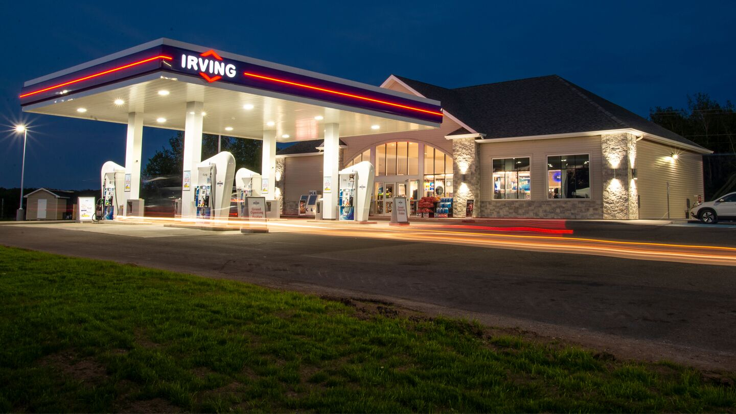 "alt=""brightly lit Irving gas station at night"""