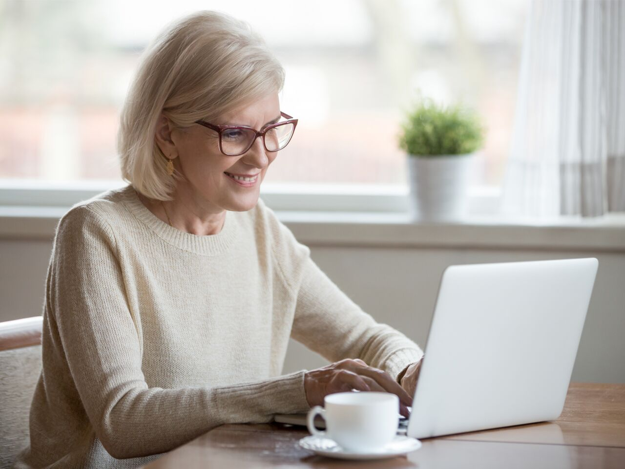 Older woman sits in front of a laptop computer, smiling warmly at the screen, with a white teacup and saucer on the side.